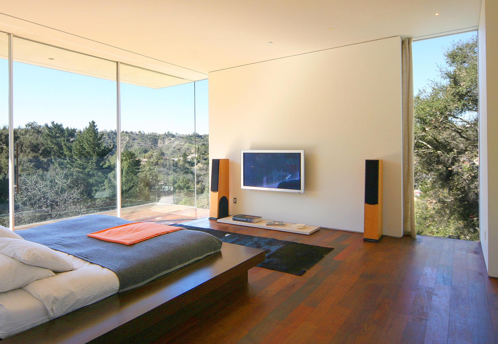 A master bedroom with natural stucco walls, floor to ceiling windows, and Brazilian walnut floors.