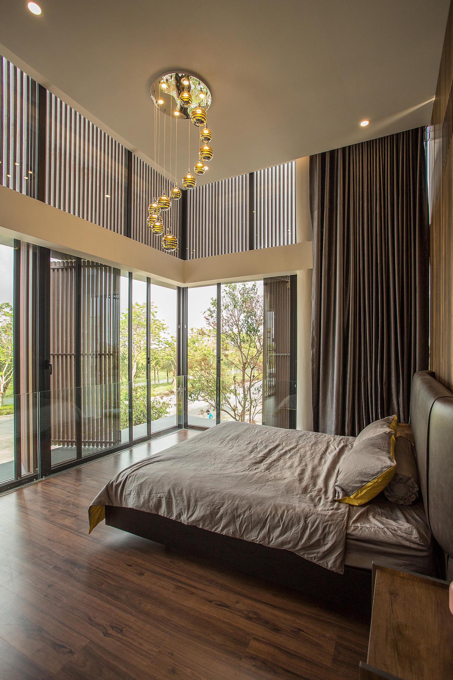 In a modern bedroom, the high ceiling allows for a grand appearance, while a wood accent wall has strips of LED lights that run from the ceiling to the floor.