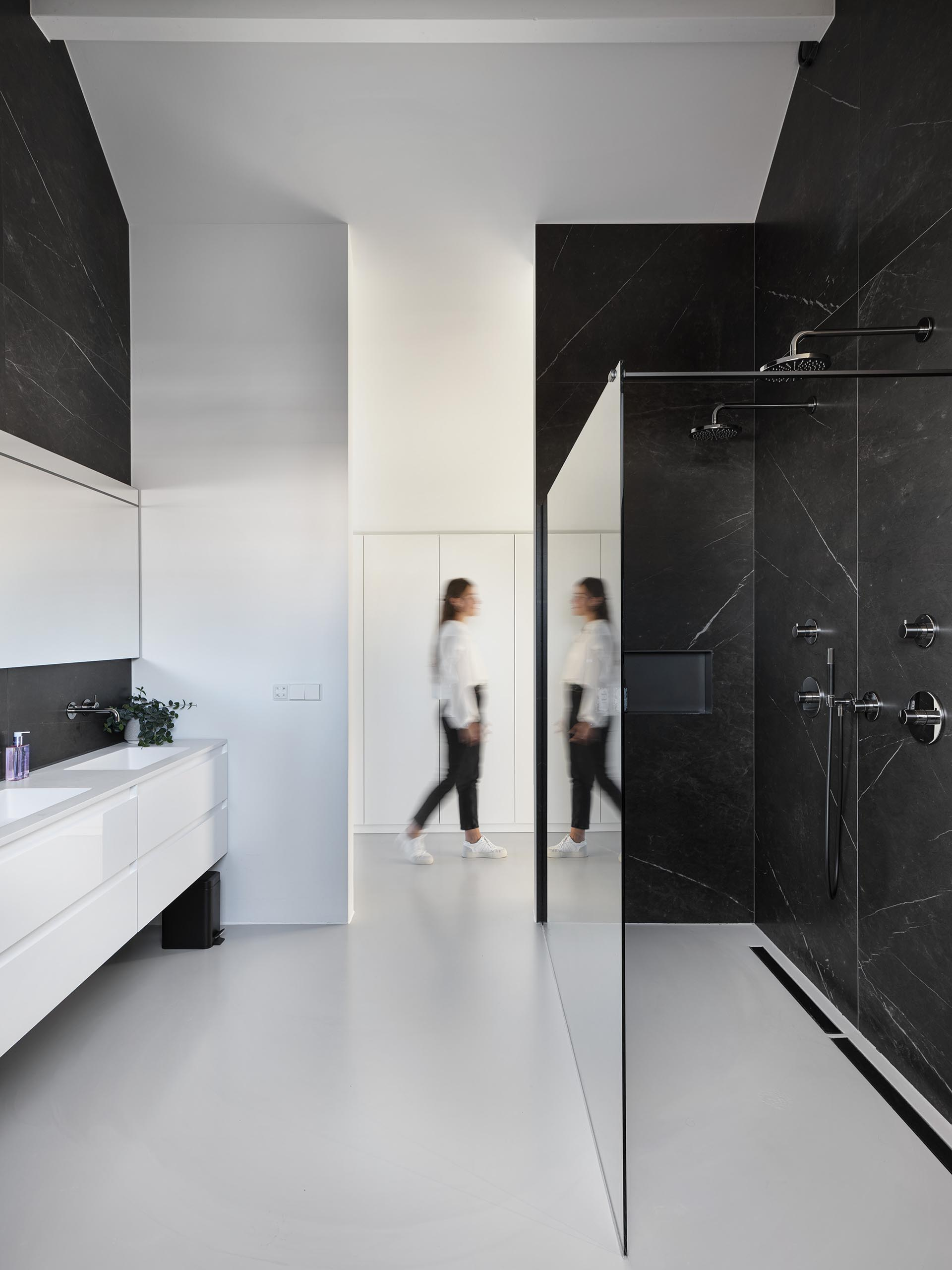 In this modern bathroom, there's black stone on the walls that provides a contrasting element to the white vanity.