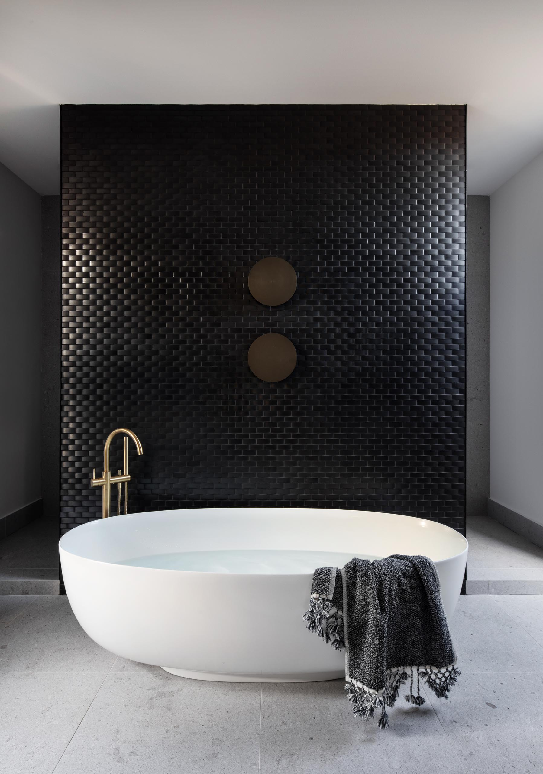 A modern bathroom with a black tile accent wall that provides a backdrop for a large oval freestanding bathtub.