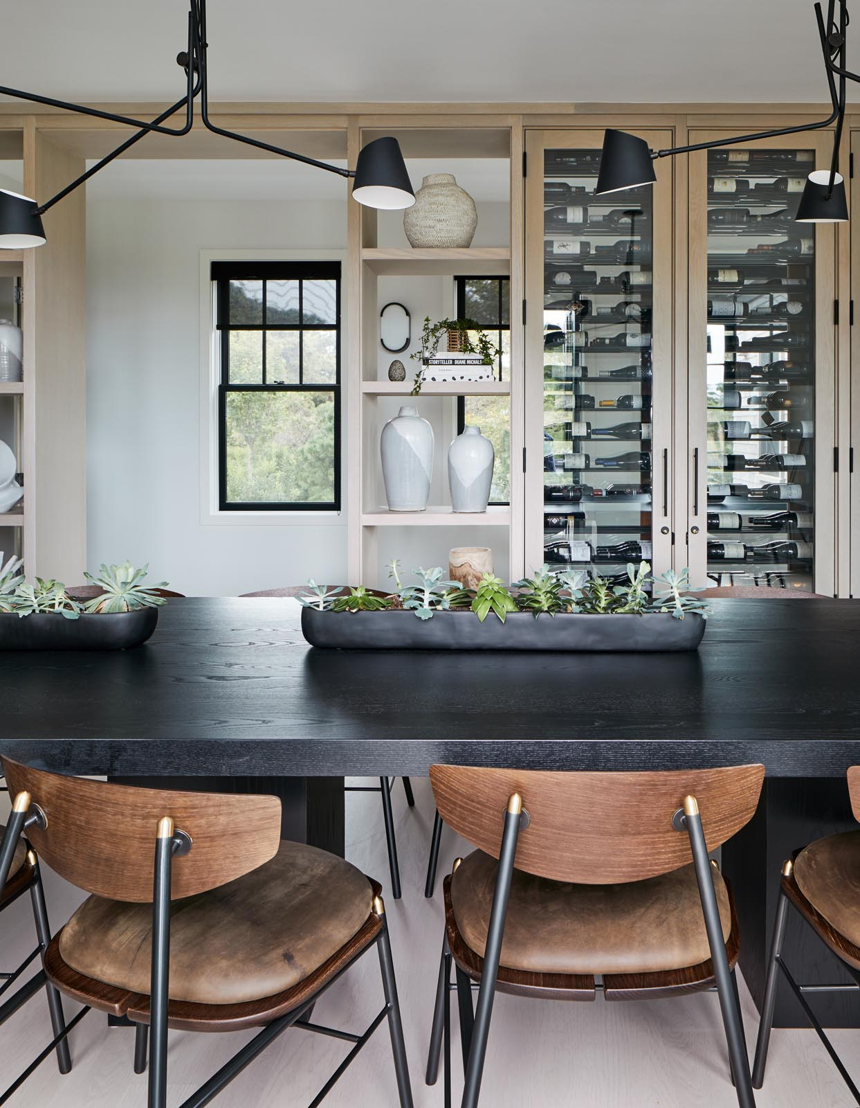In this dining area, there's a custom designed wood shelving unit that includes glass front cabinets that show off a wine collection.
