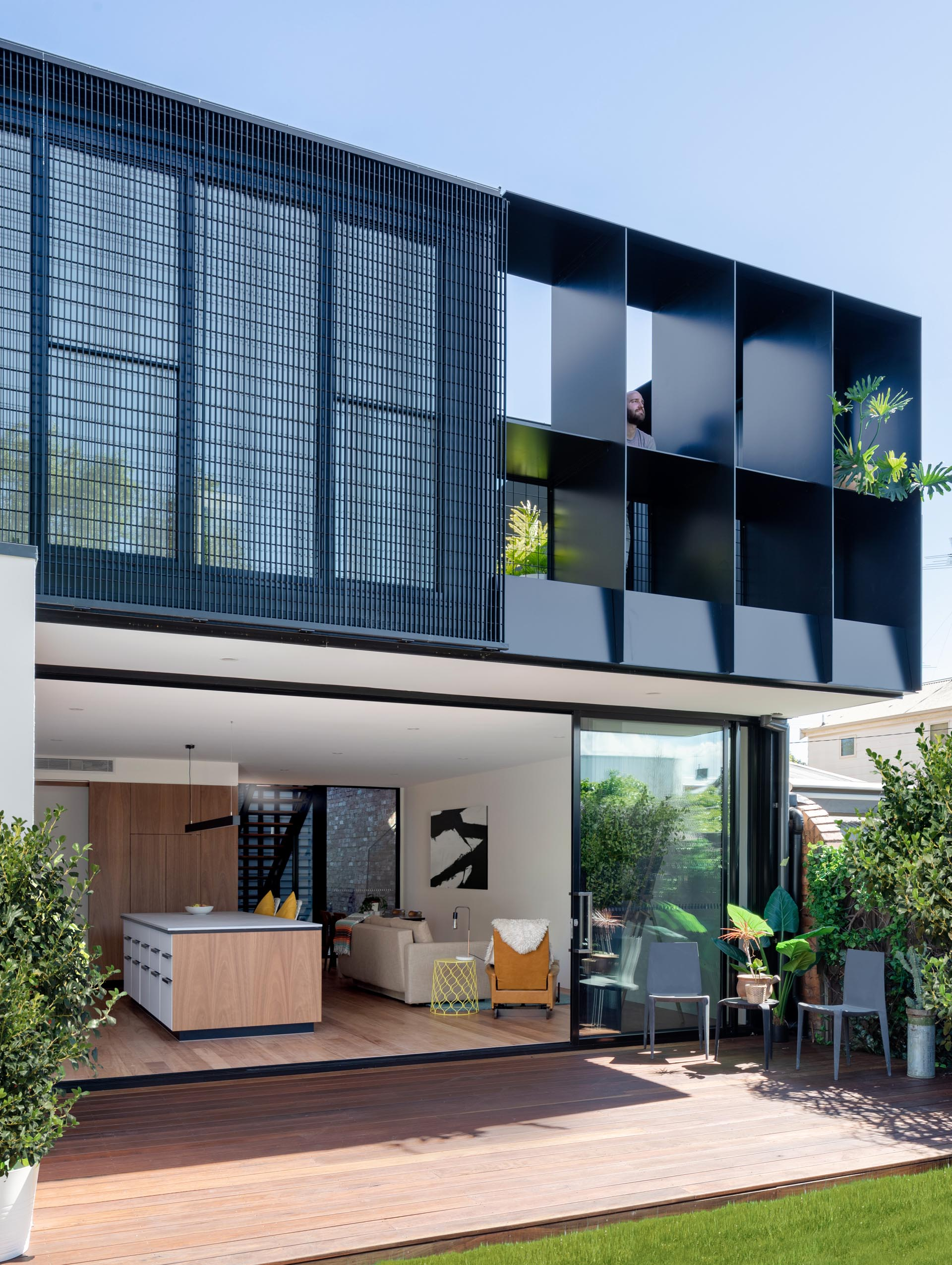 A modern house extension with a sliding glass wall that opens to the backyard, which provides a view of the rear dark gray corrugated metal extension.