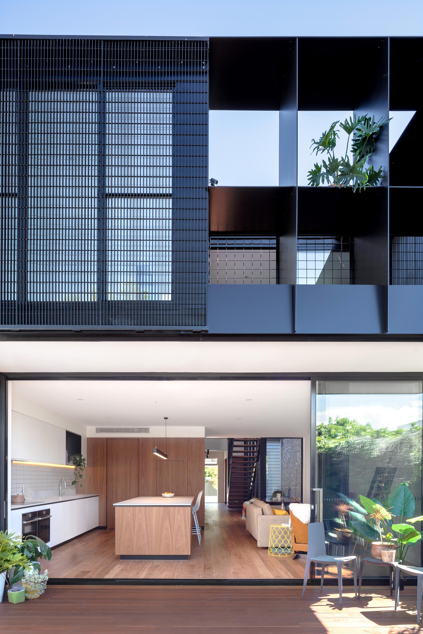 A modern house extension with a sliding glass wall that opens to the backyard, which provides a view of the rear dark gray corrugated metal addition.