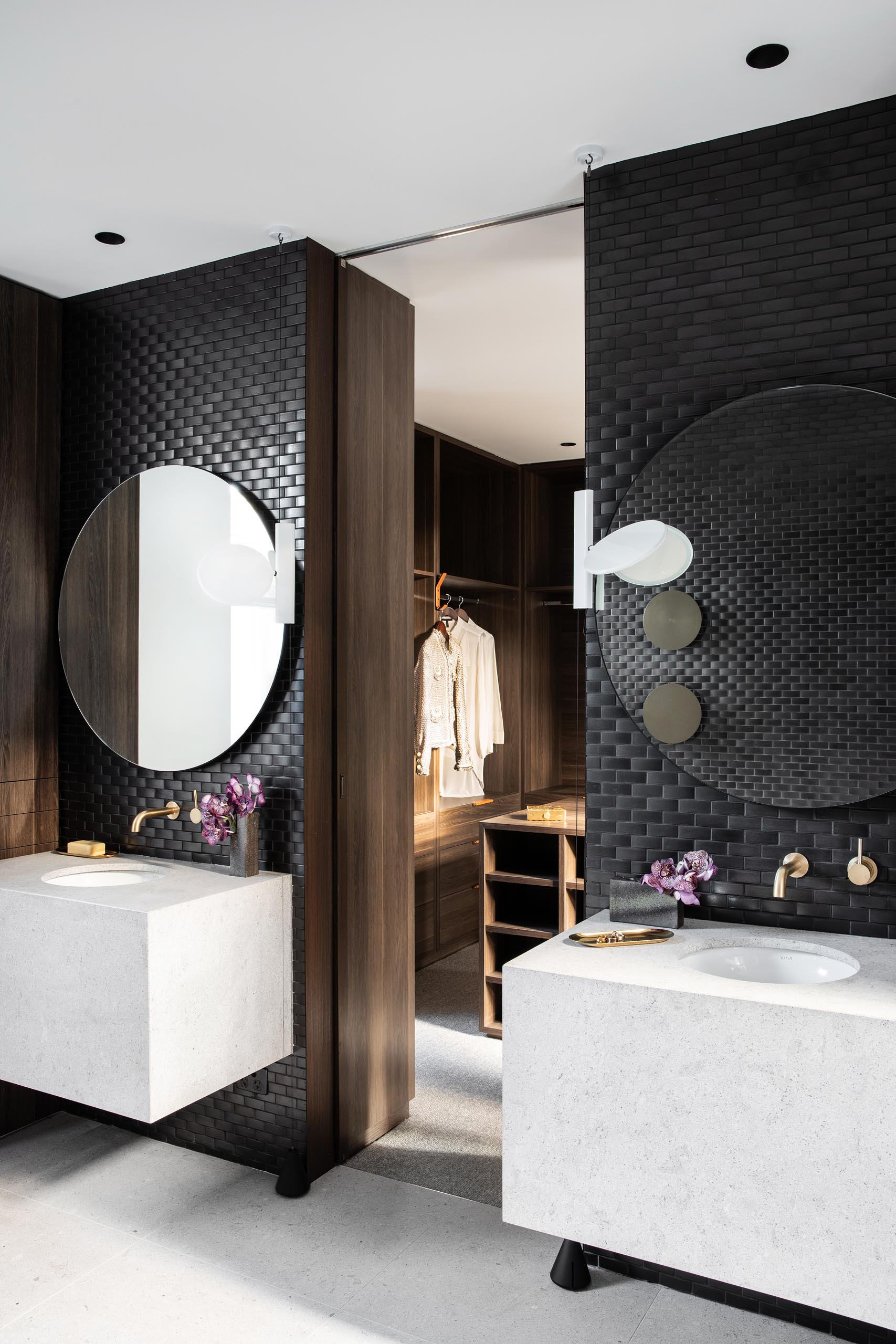In the master bathroom, black tiles cover walls, while round mirrors hang above white vanities with undermount sinks.