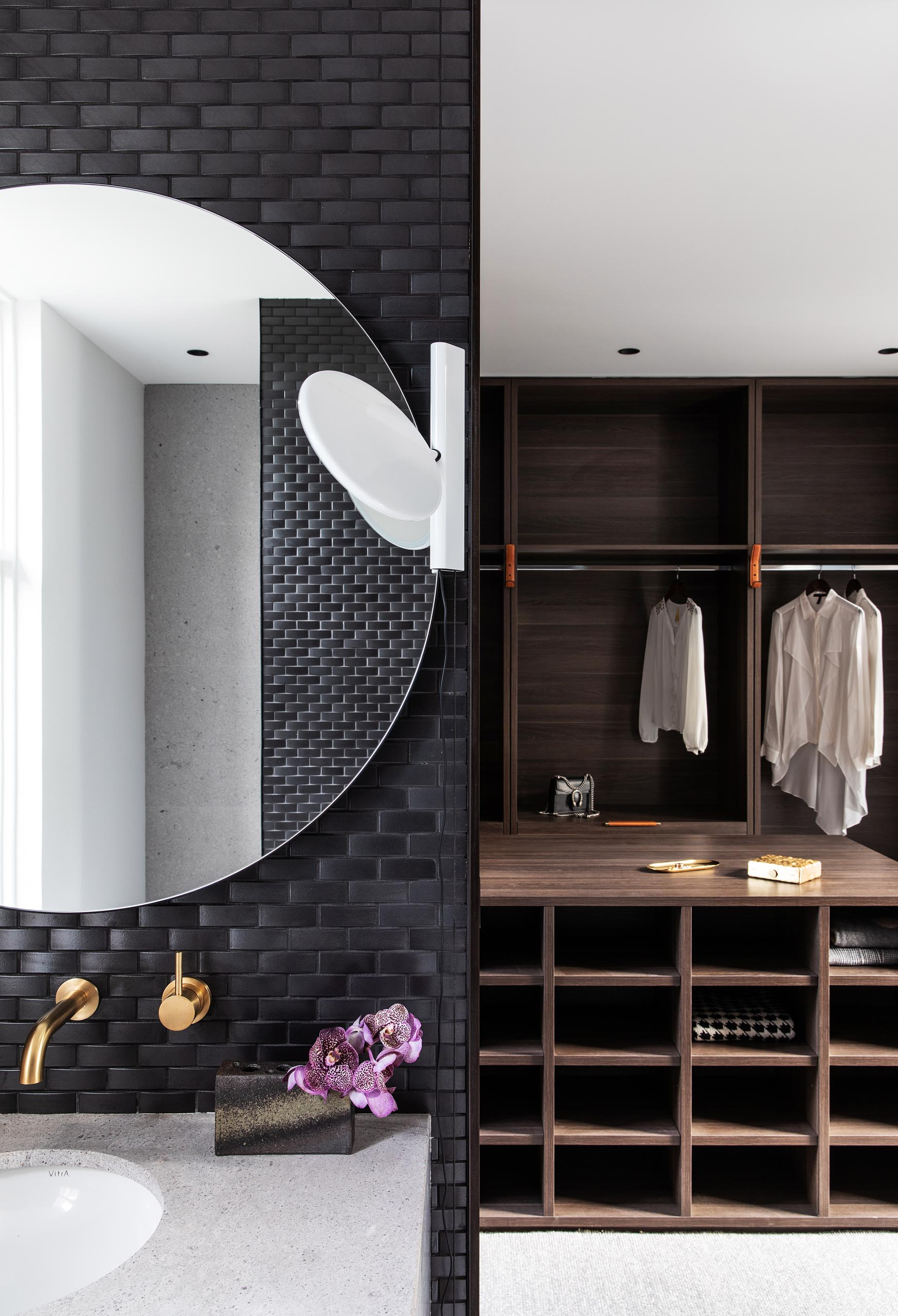In the master bathroom, black tiles cover walls, while round mirrors hang above white vanities with undermount sinks. There's also a walk-in closet with dark wood cabinetry.