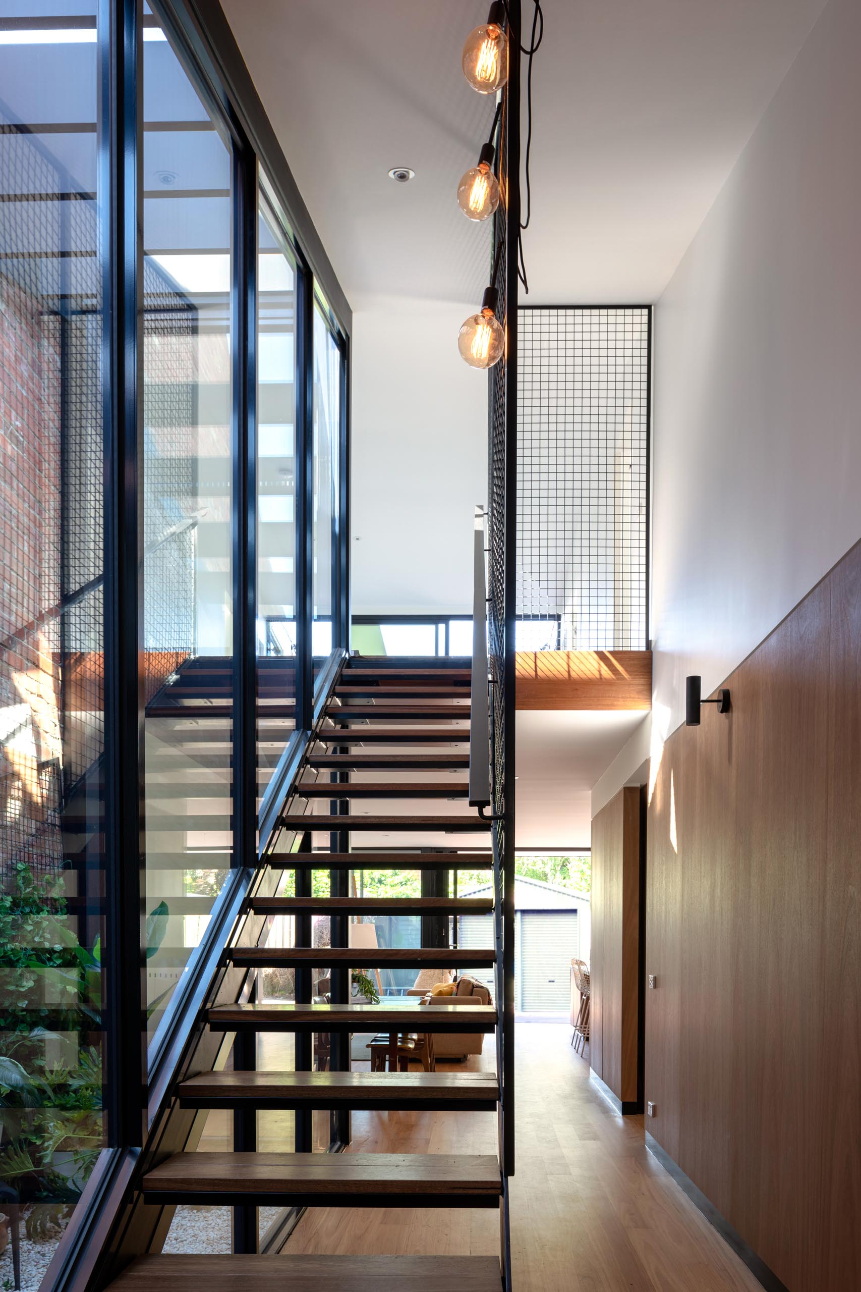 A modern wood and steel staircase that runs alongside a wall of glass.