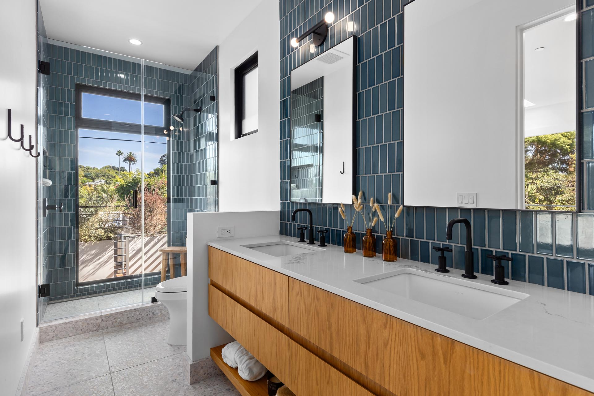 In this modern bathroom, blue tiles are featured on the wall and in the shower, and there's also a wood vanity with double sinks.