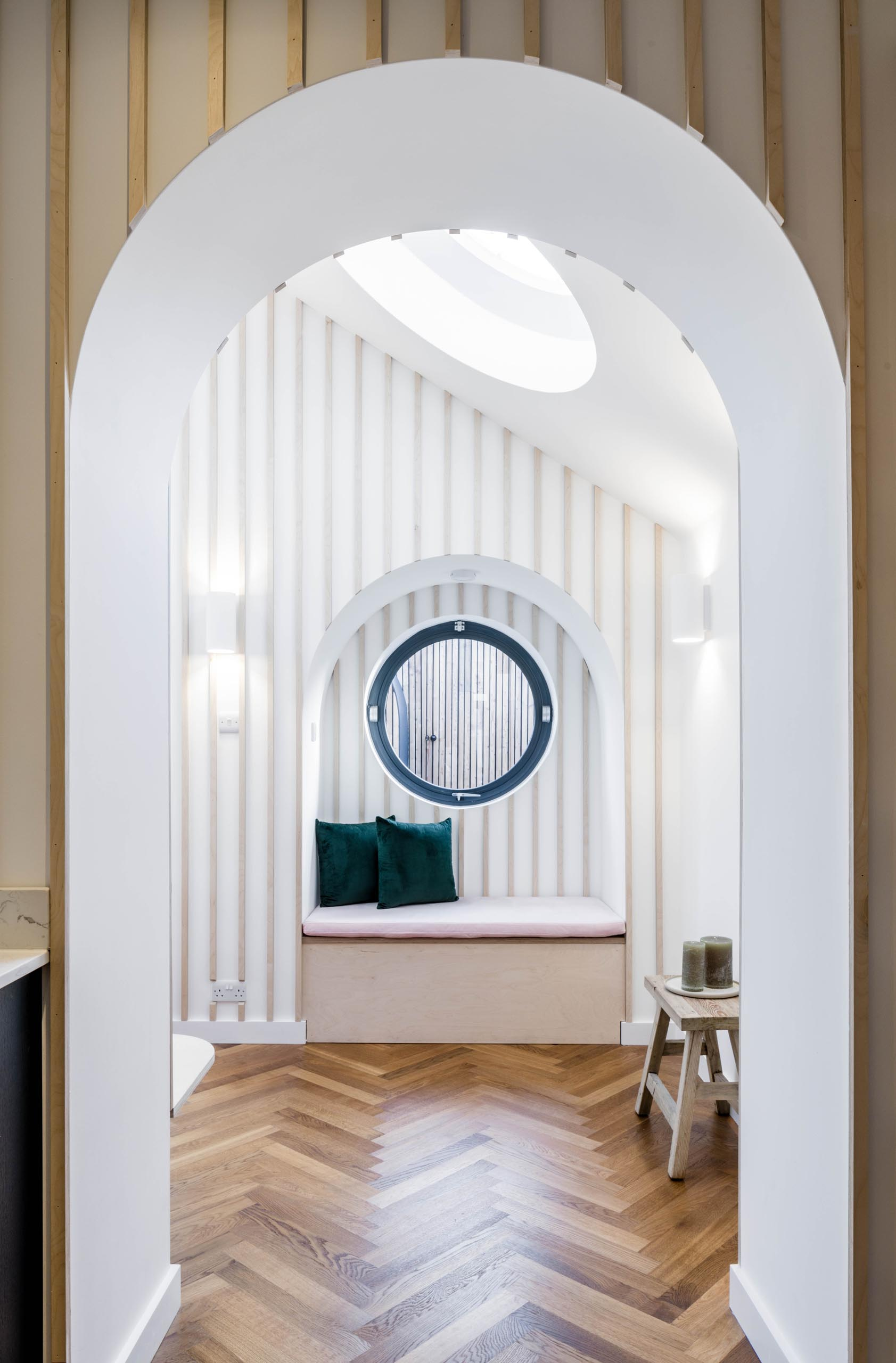 A built-in window bench sits below a round black-framed window.