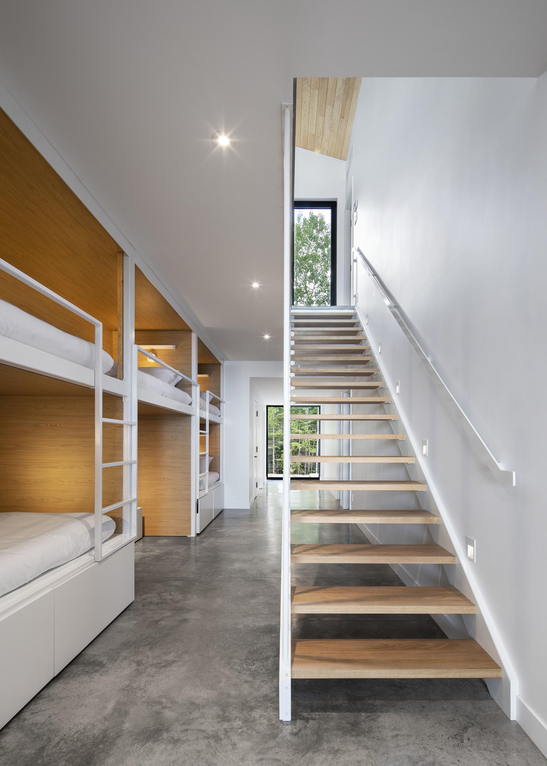 At the bottom of these modern stairs stairs and open to the hallway, are multiple sets of bunk beds. These bunk beds have a wood interior, with white suppers and ladders that match the walls.