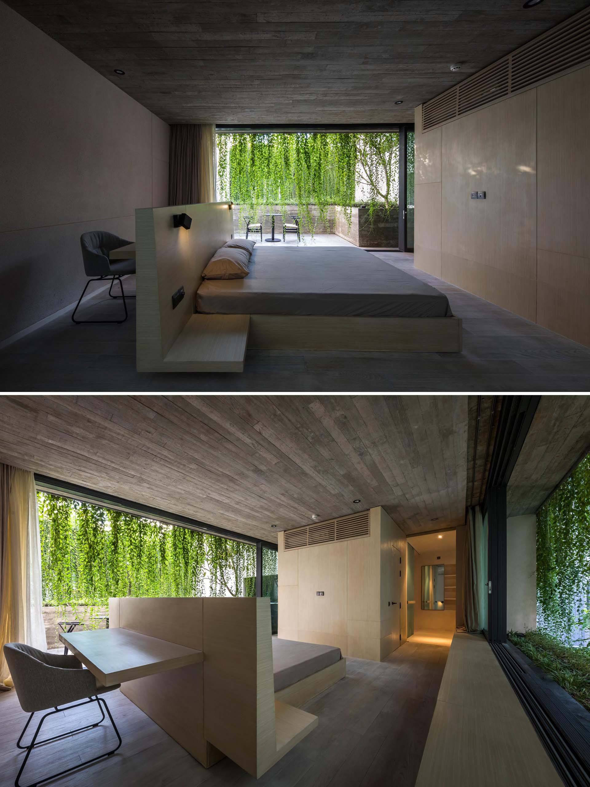 A minimalist bedroom with concrete walls, and a bed frame that incorporates a desk behind the headboard.