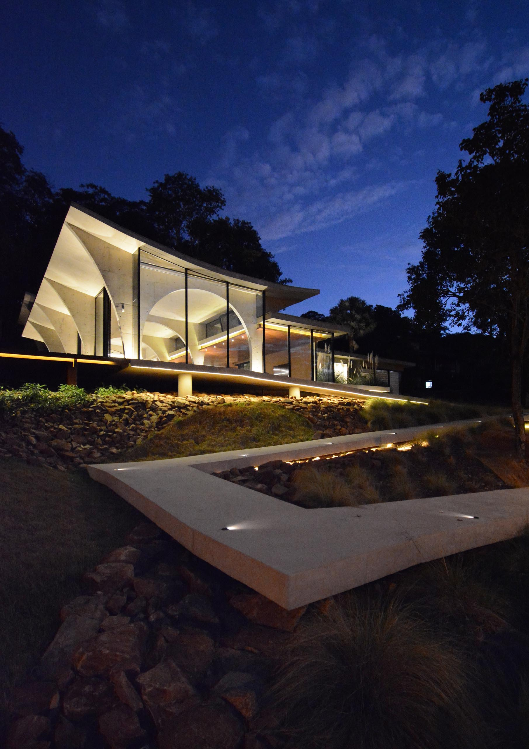 This modern concrete home features numerous arches, which are especially visible at night as the interior light highlights the curves.