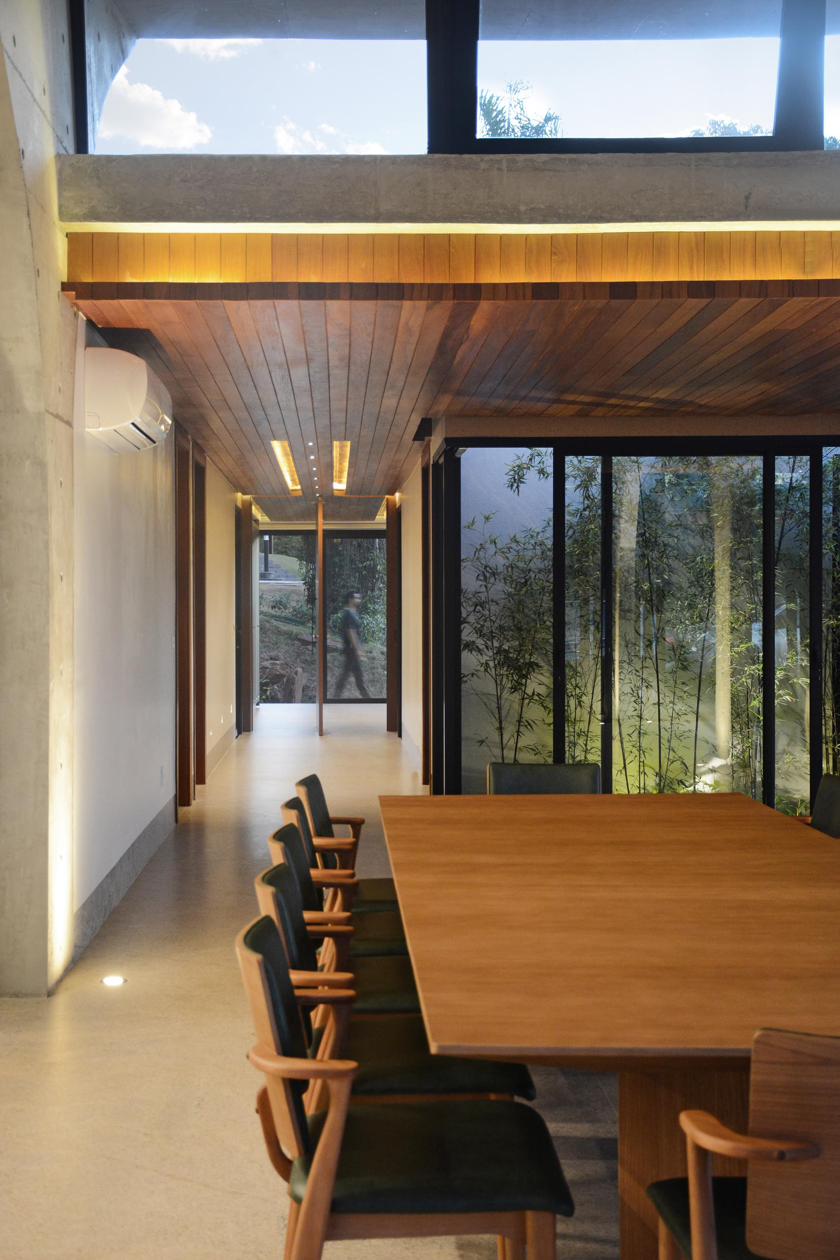 A pivoting front door welcomes people to the home, while a wood ceiling with lighting adds a sense of warmth to the interior.
