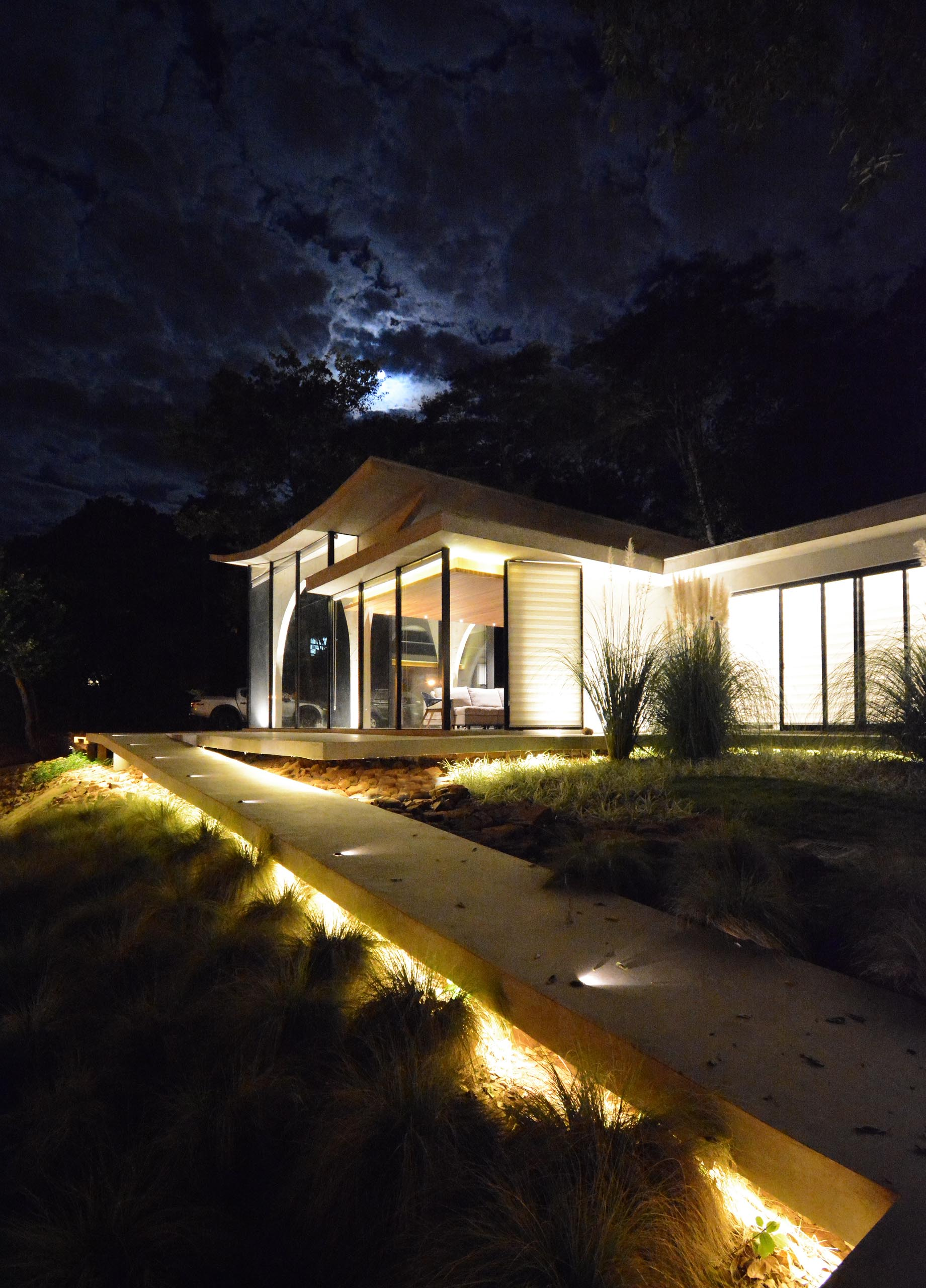 At the front of this modern home, there's a winding concrete path that's lit up at night, guiding people from the road up to the front door.