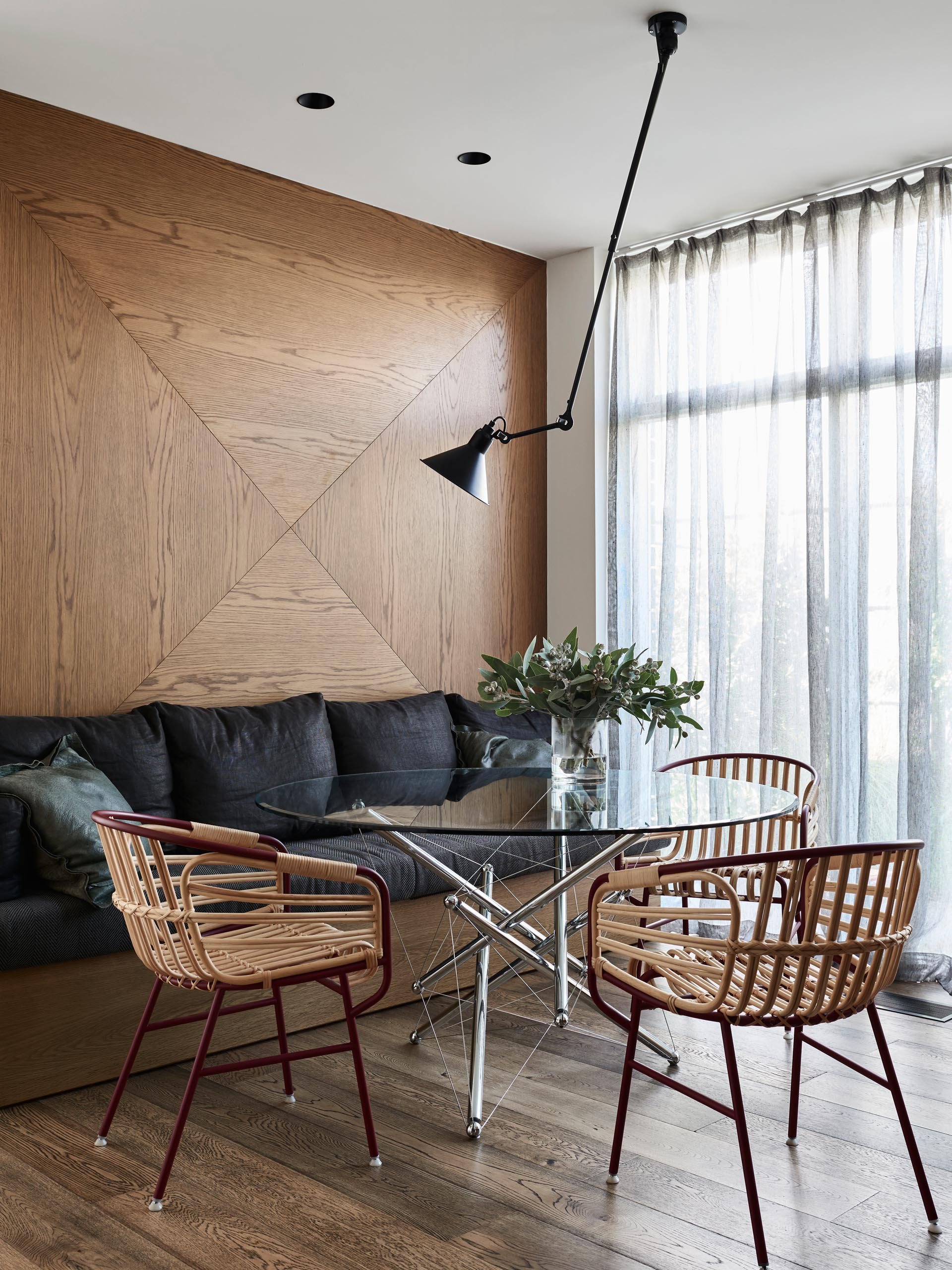 In this dining room, a wood accent wall provides a backdrop for a built-in bench with black cushions.