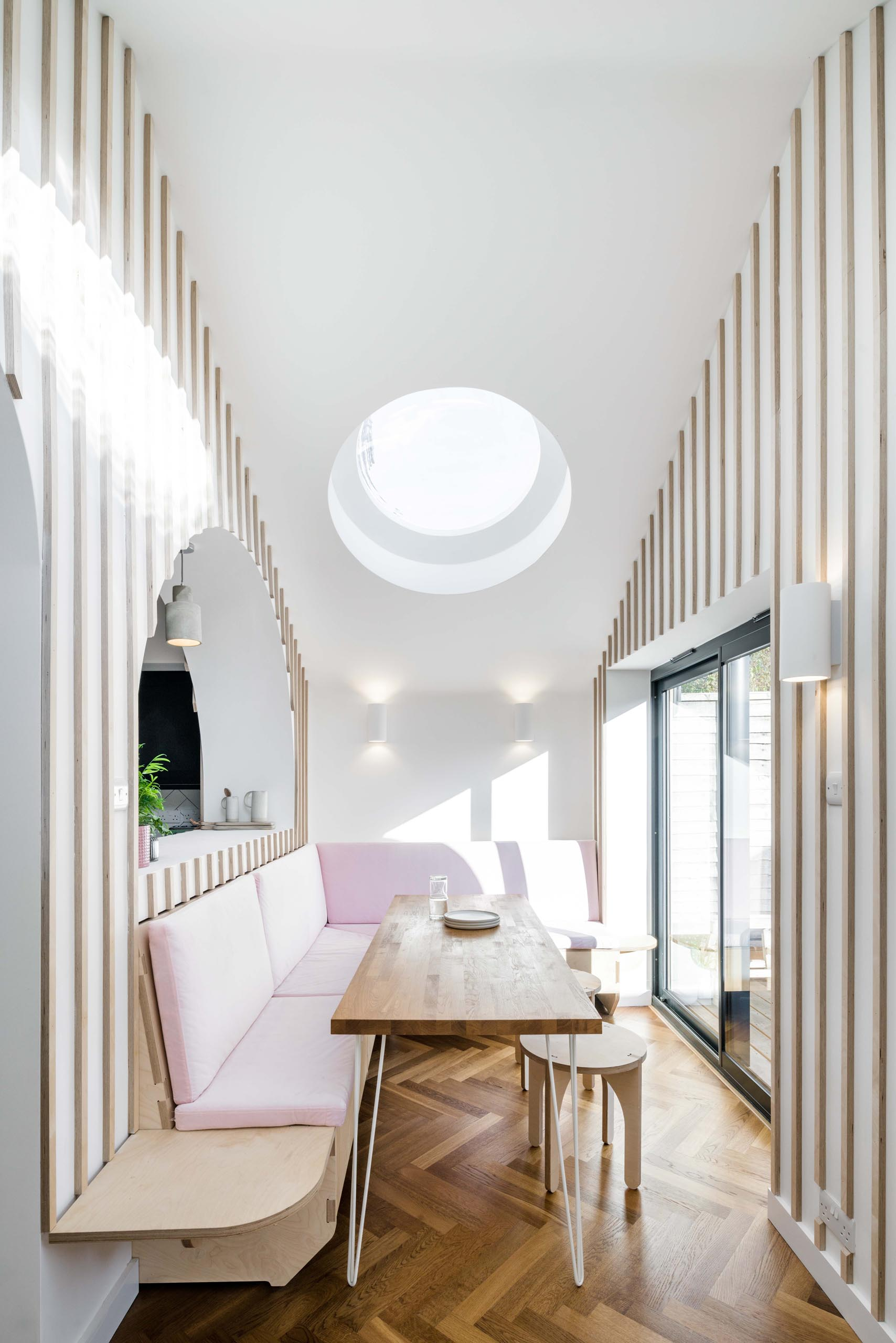 A modern dining area that has built-in banquettes that wrap around the corner of the space, while round skylights add a touch of natural light.
