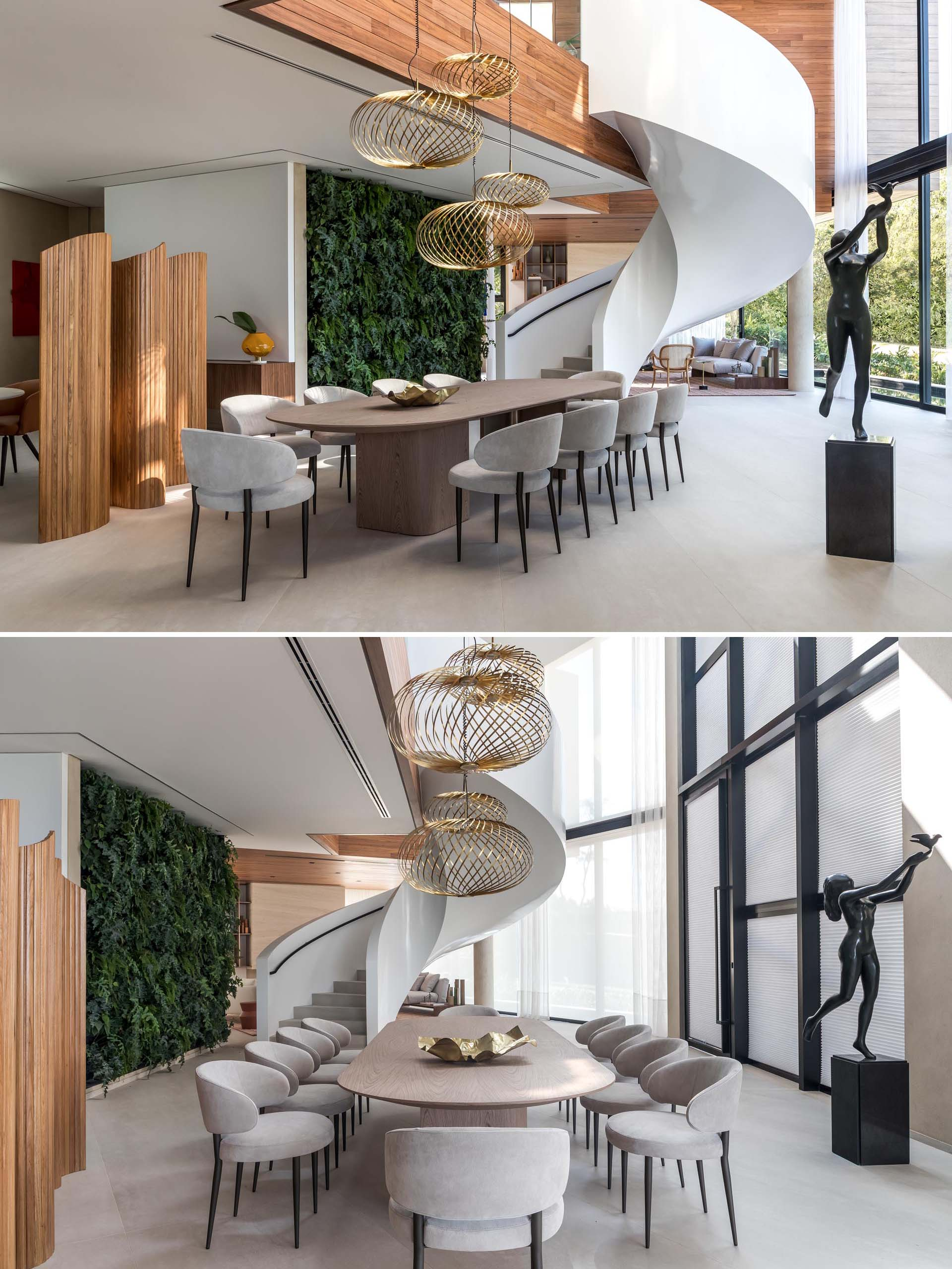 Sculptural metallic pendant lights hang above the rounded dining table in this modern dining room, while spiral stairs and a green wall separate the dining area from the living room.