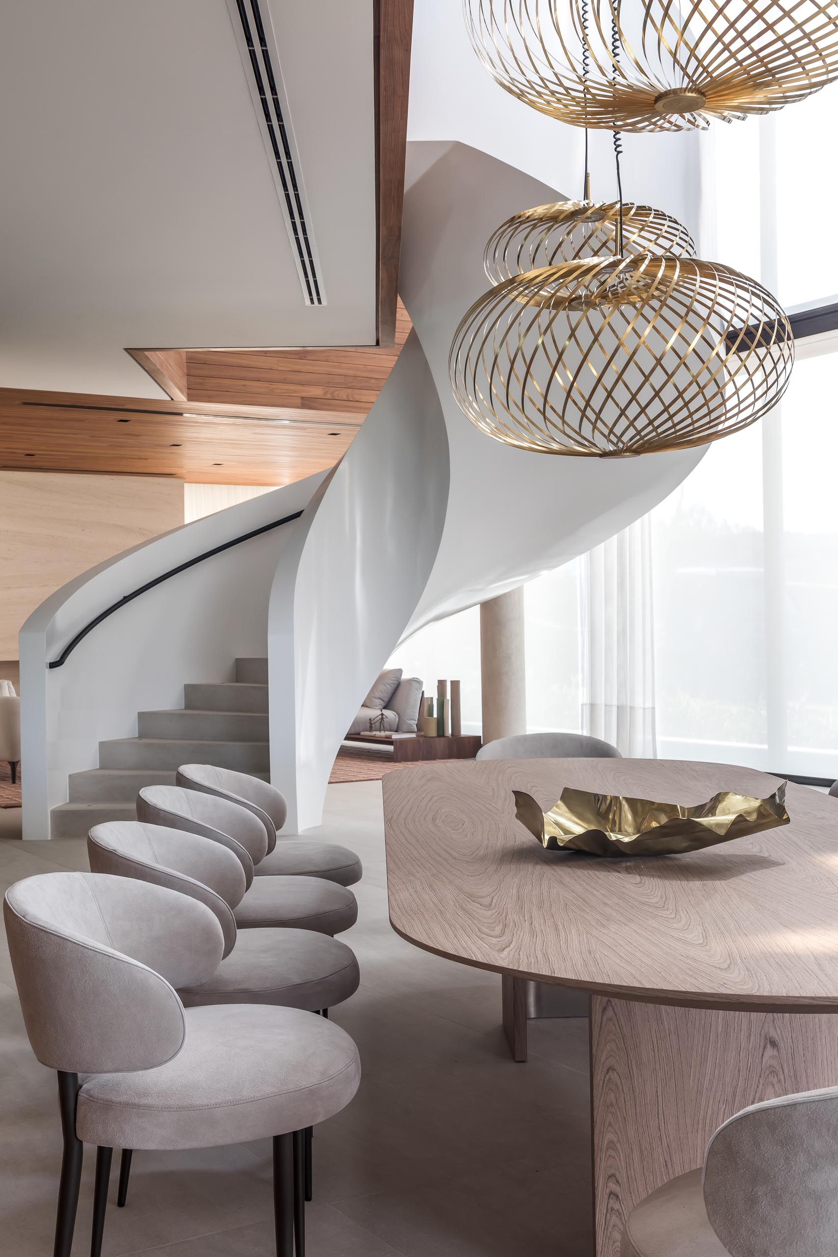 Sculptural metallic pendant lights hang above the rounded dining table in this modern dining room.