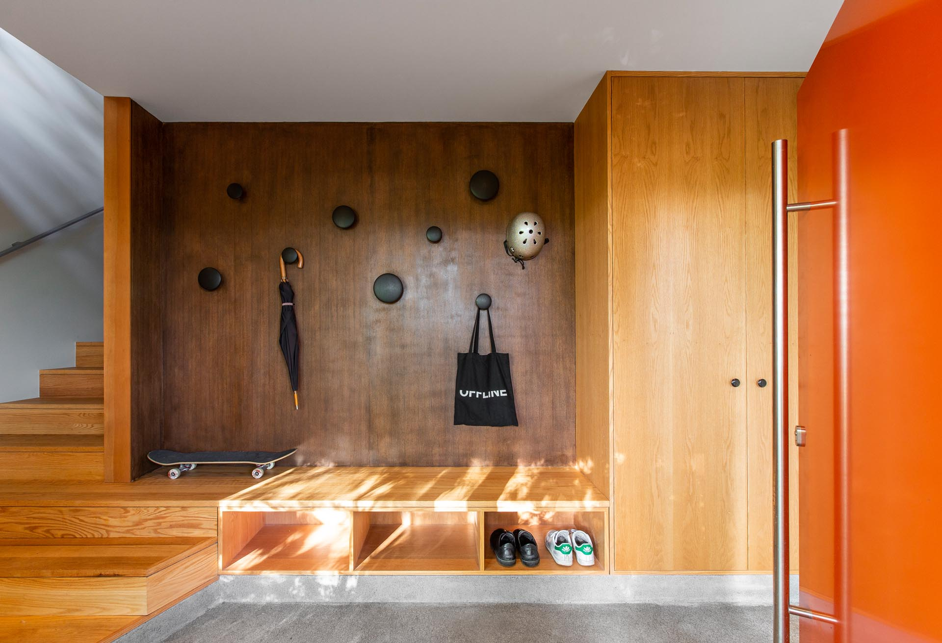 A black walnut plywood wall has been paired with red oak casework to create a modern entryway.
