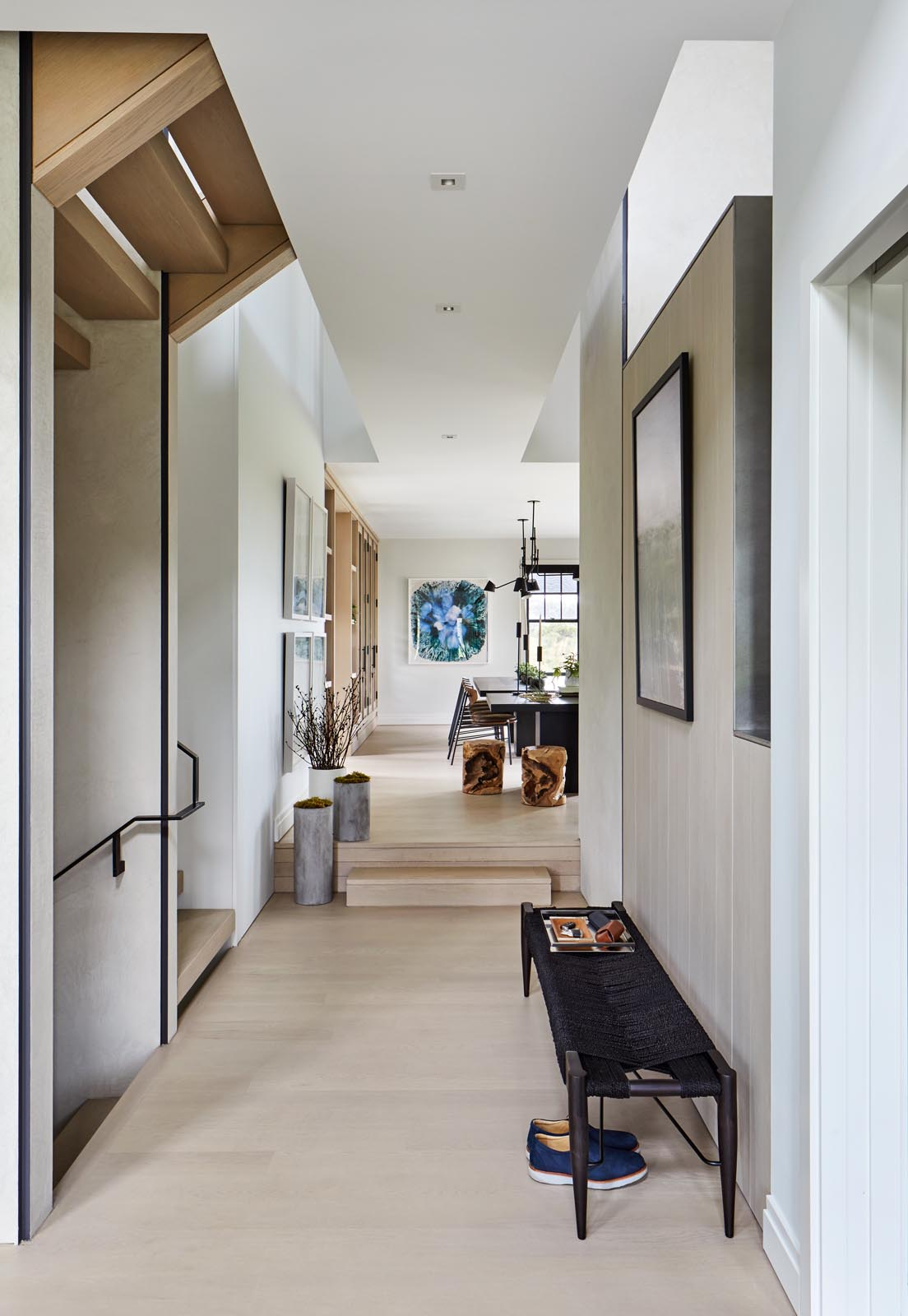 A modern entryway furnished with a simple black bench and artwork.