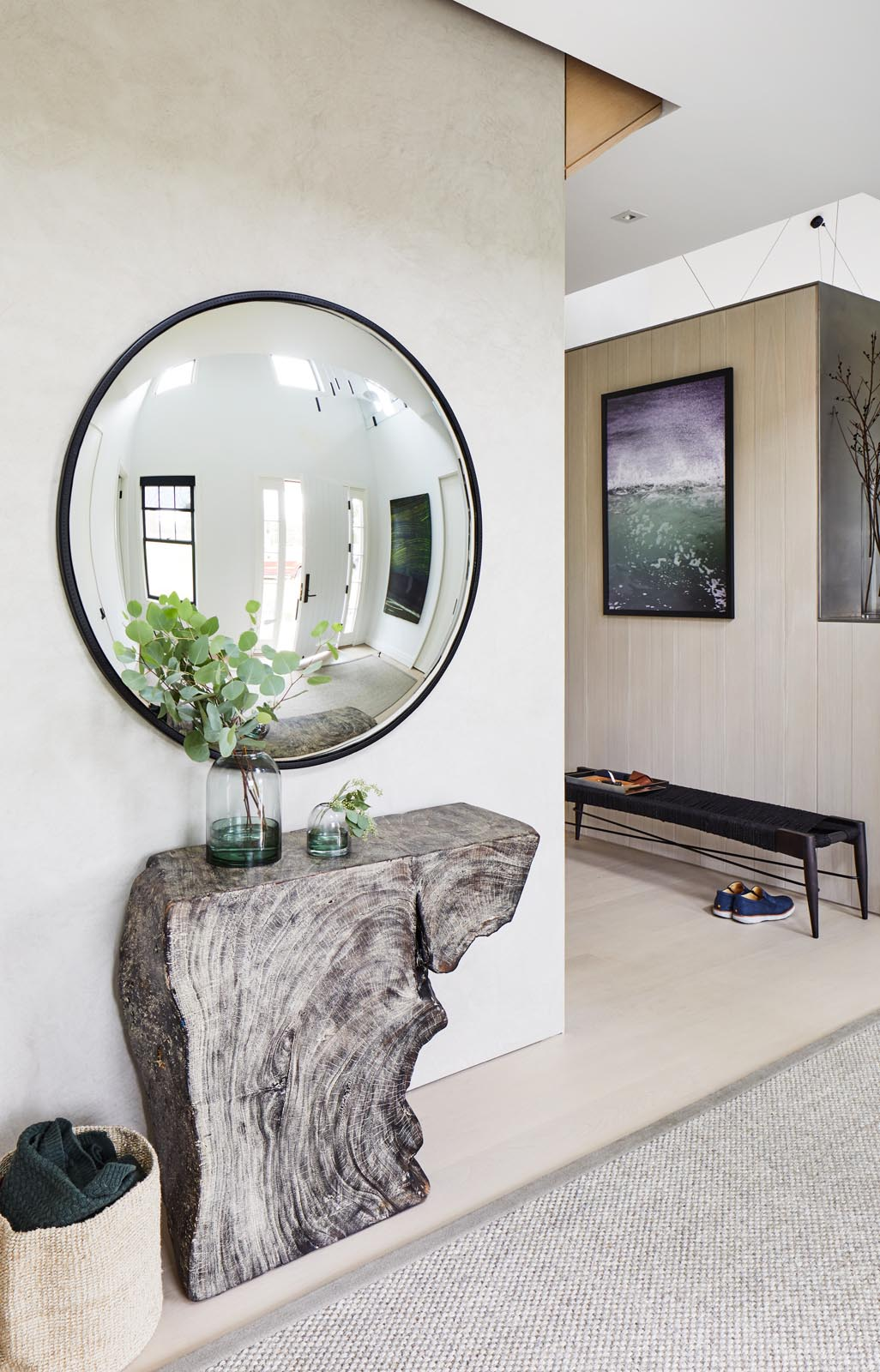 A modern entryway with a live edge wood console table and a round mirror with a black frame.