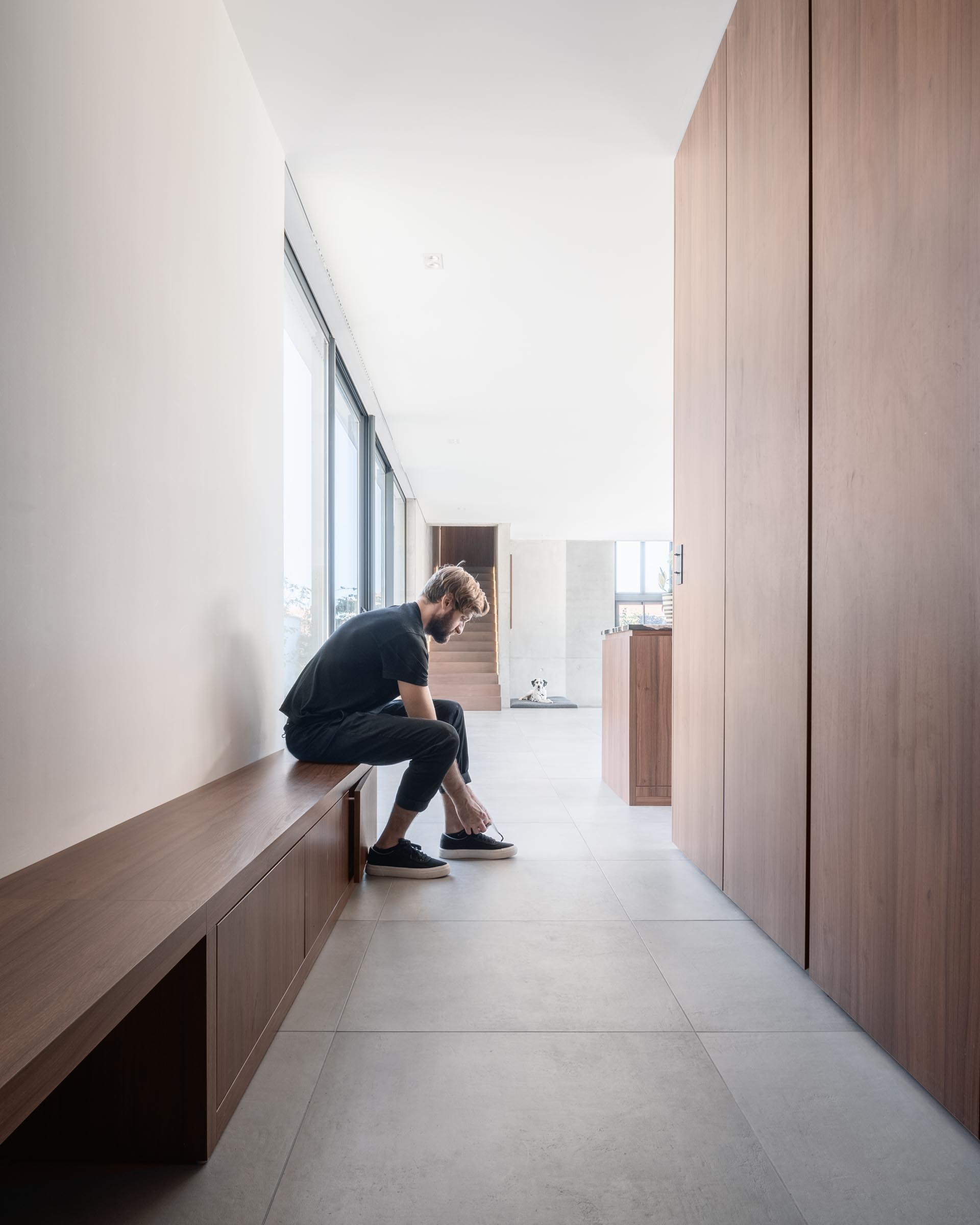 This modern entryway has a long wood bench, and on the opposite wall is a powder room and cabinets for storing jackets.