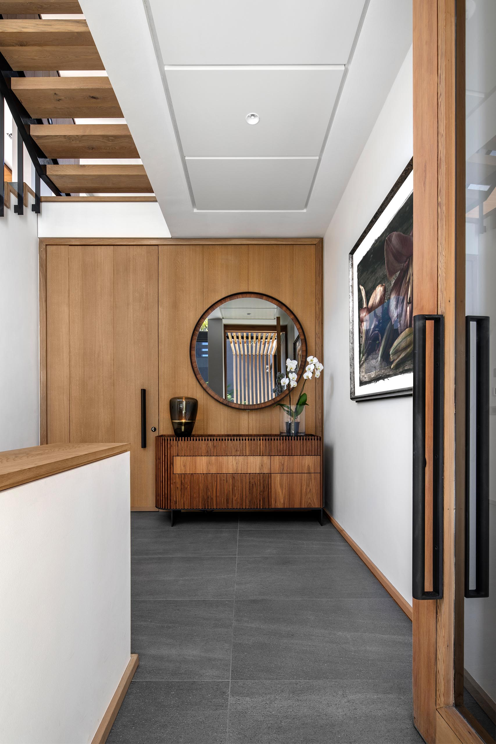 A modern entryway furnished with a wood console table, artwork, and a round mirror.
