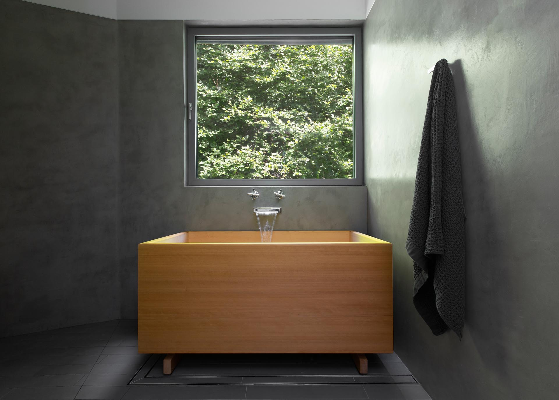 A modern bathroom with dark gray walls and a wood Japanese soaking tub.