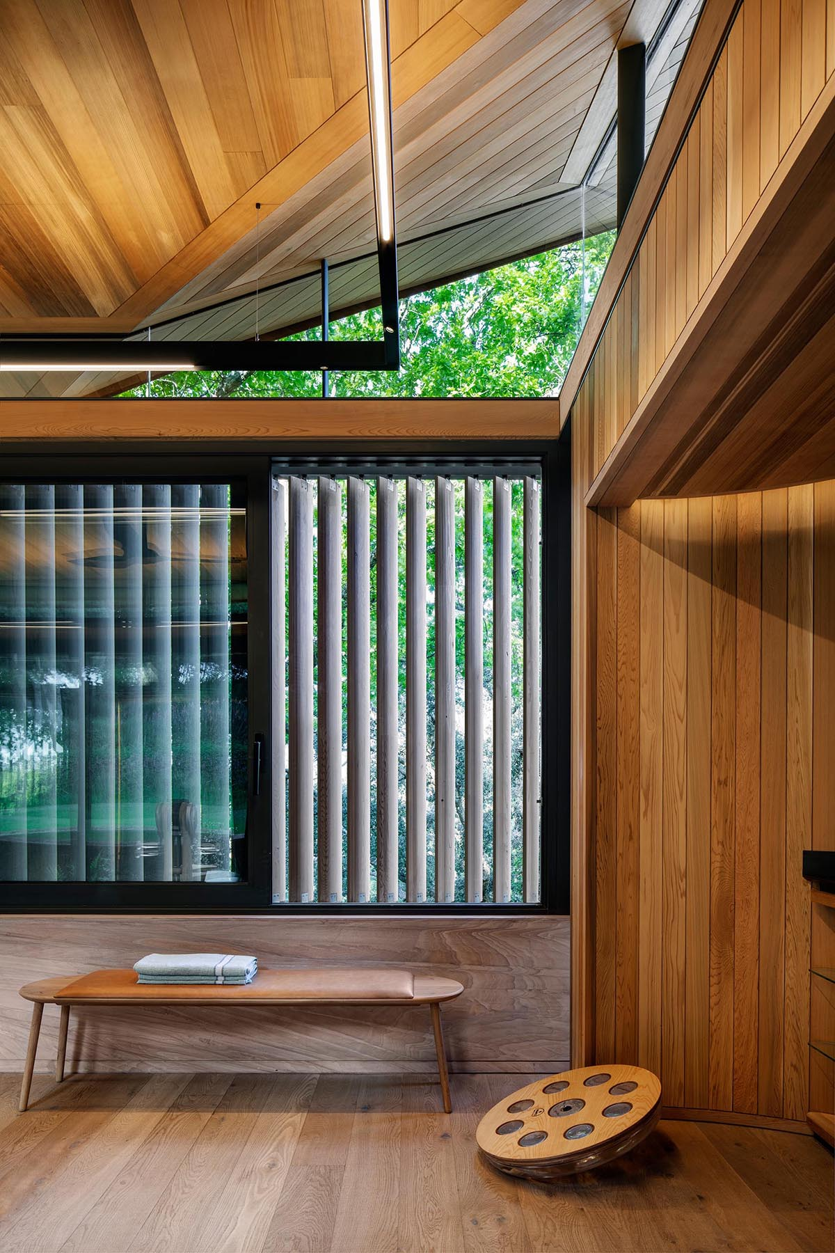 A home gym with aero-foil timber screens that provide privacy when needed.
