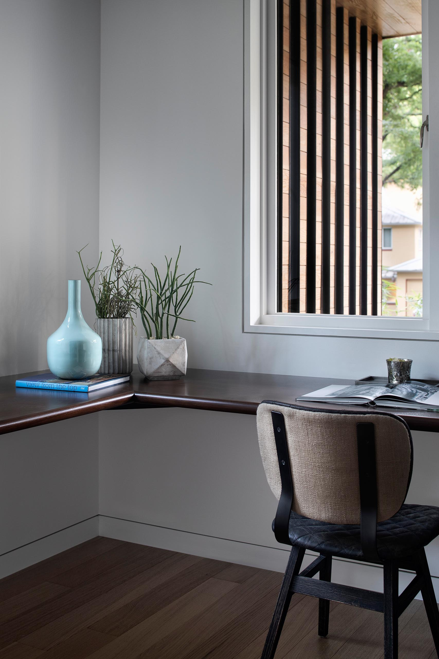 A modern home office with a dark wood floating desk.