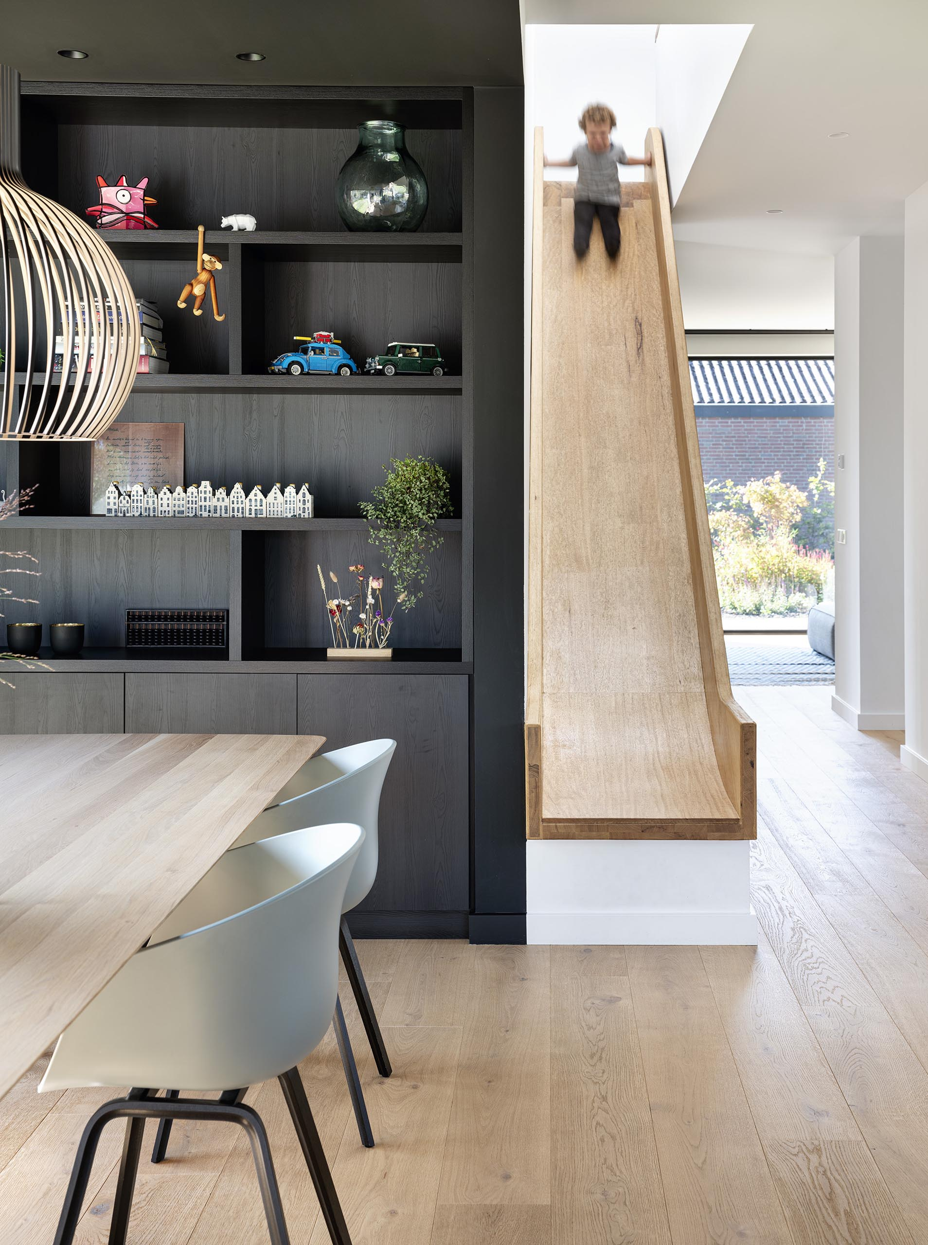 A fun element in the form of a wood slide is a quick way to reach the living spaces from the upper floor of the home.