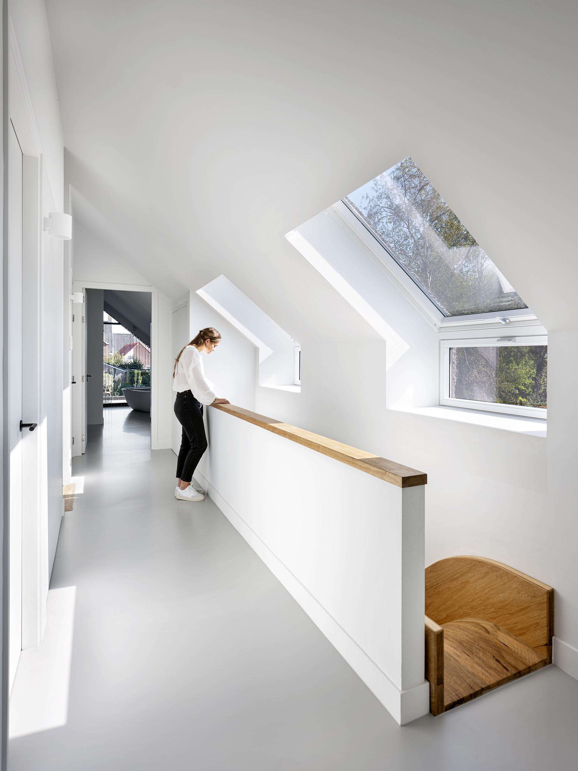 A modern house with an open hallway that connects to the bedrooms and shows the top of an indoor wood slide.
