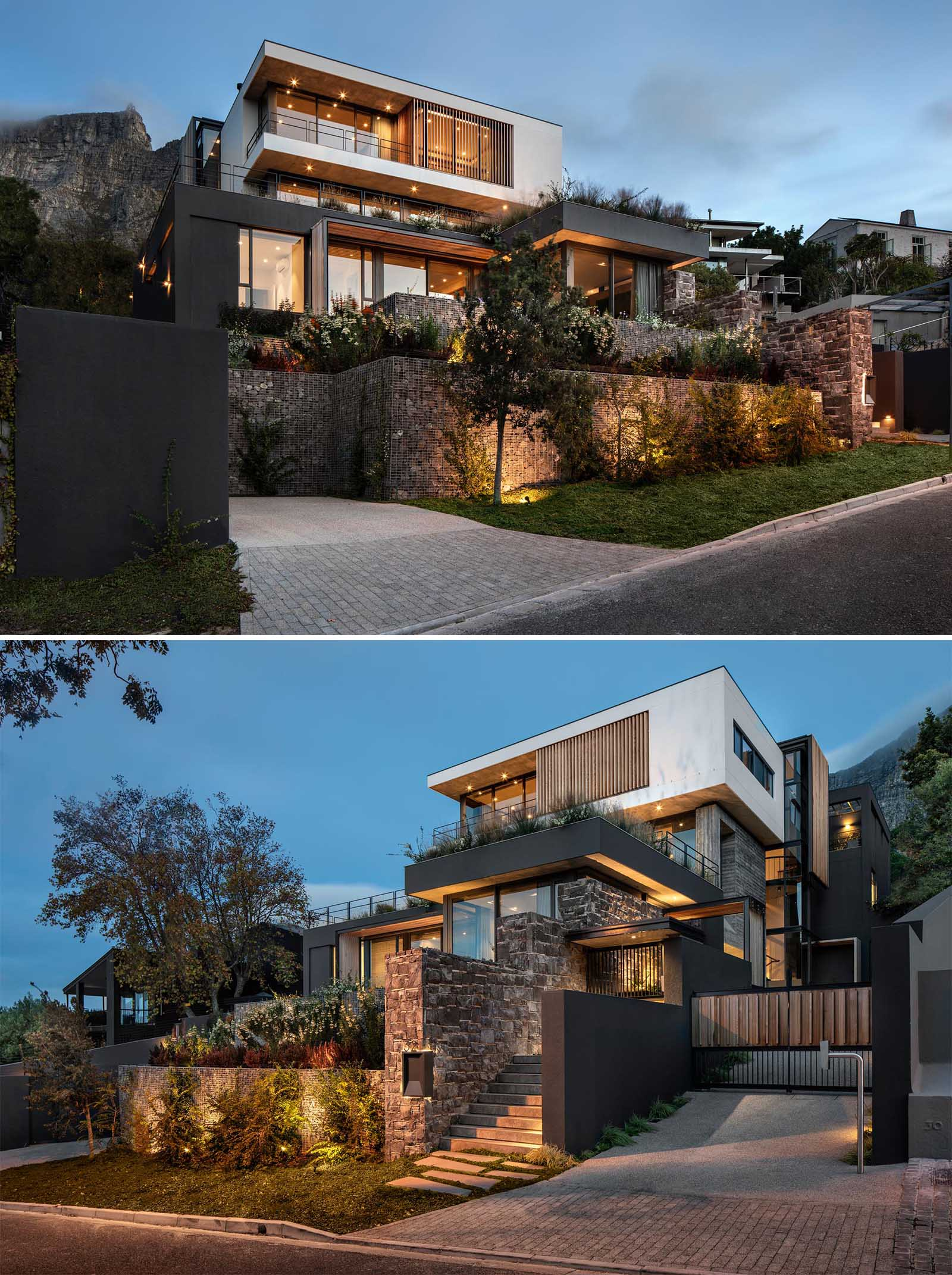 Stone and gabion walls with plants are lit up by exterior lighting at the front of this modern home, while wood slats add a natural element on the upper level of the home.