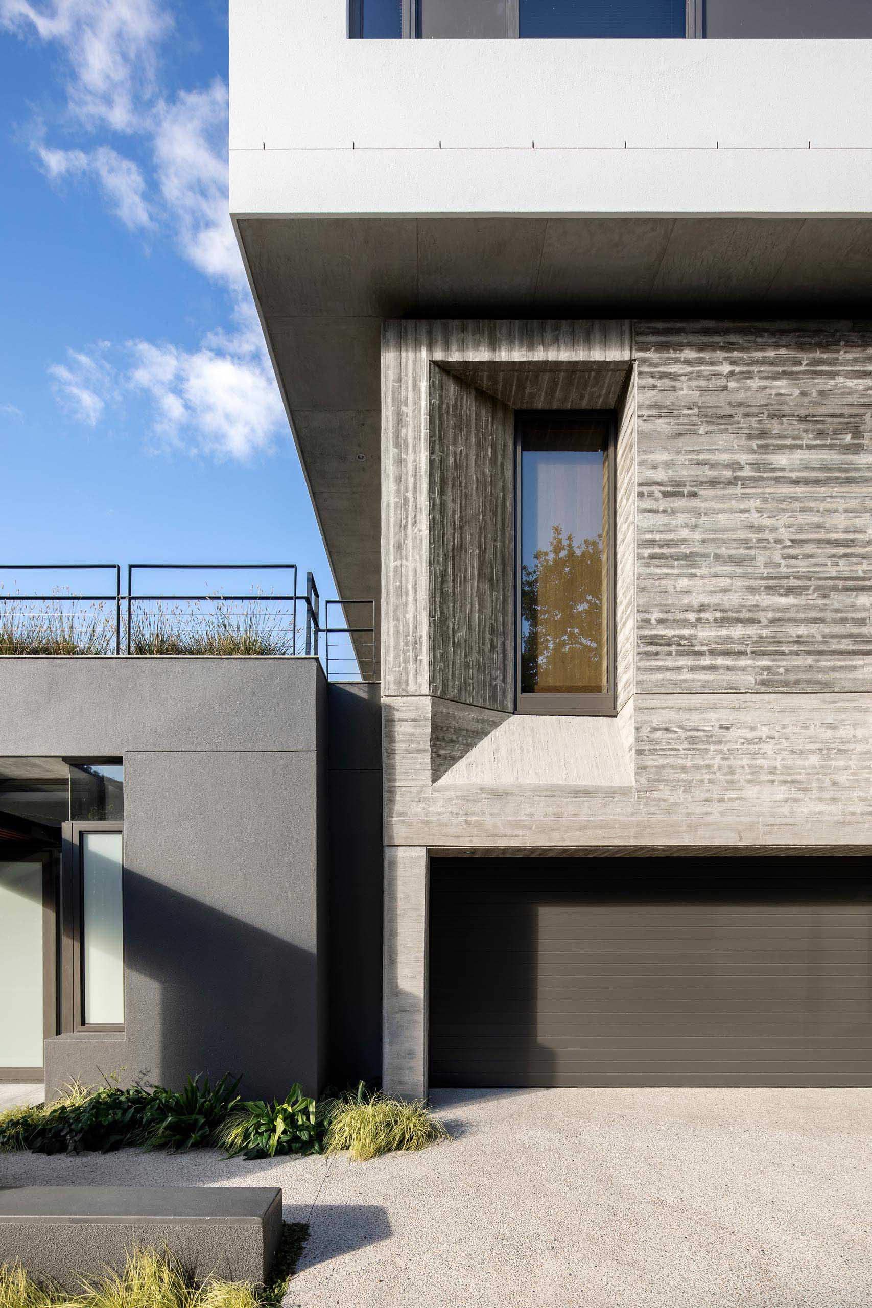 A modern house with a concrete and black exterior.