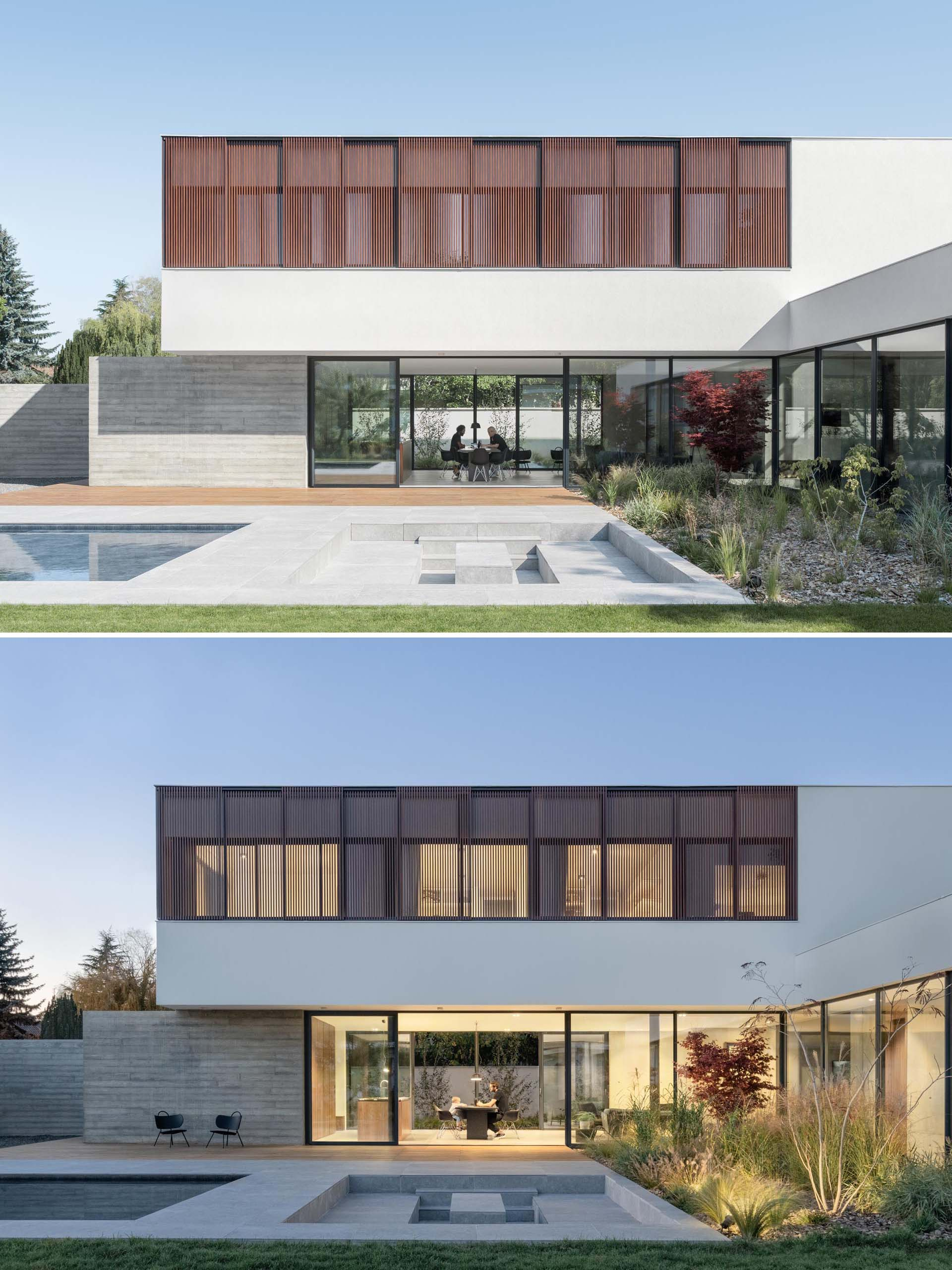 Large sliding glass windows transforming the living room into a huge terrace opening onto a green space, erasing the separation between inside and outside.