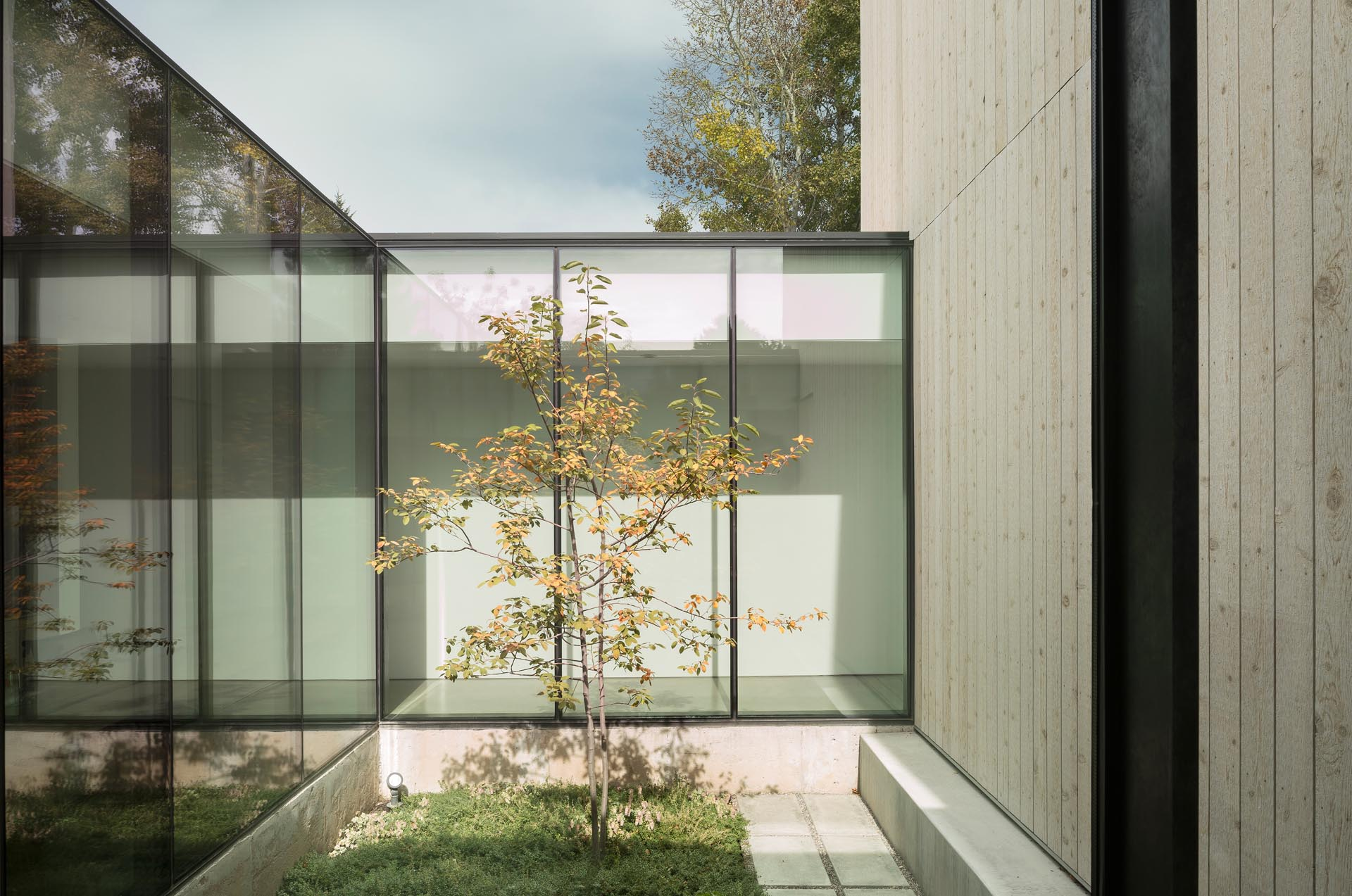 A modern home with a long hallway, floor-to-ceiling windows, and concrete floors.