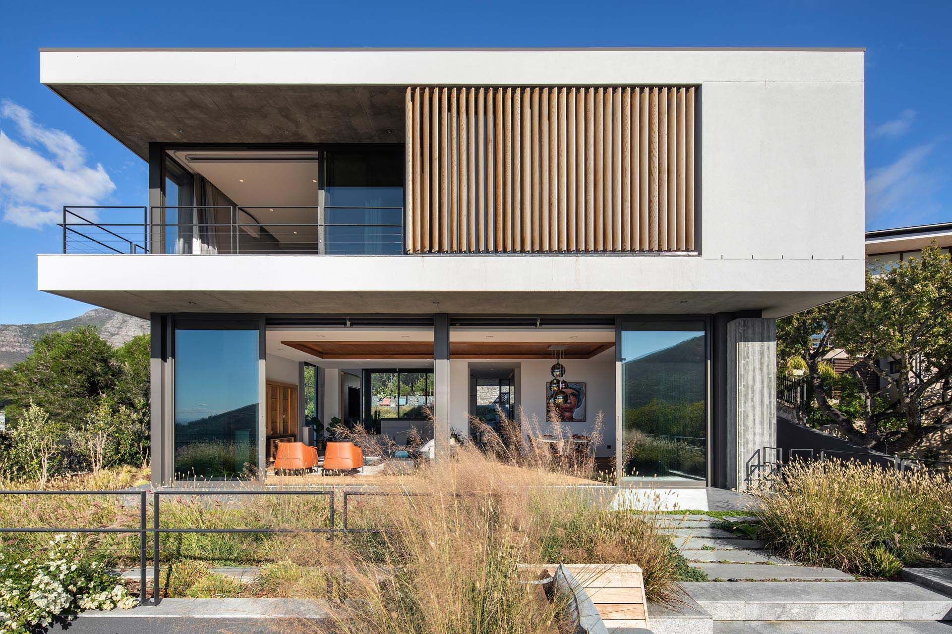 A modern home with an upper level that has wood slats and a covered balcony.