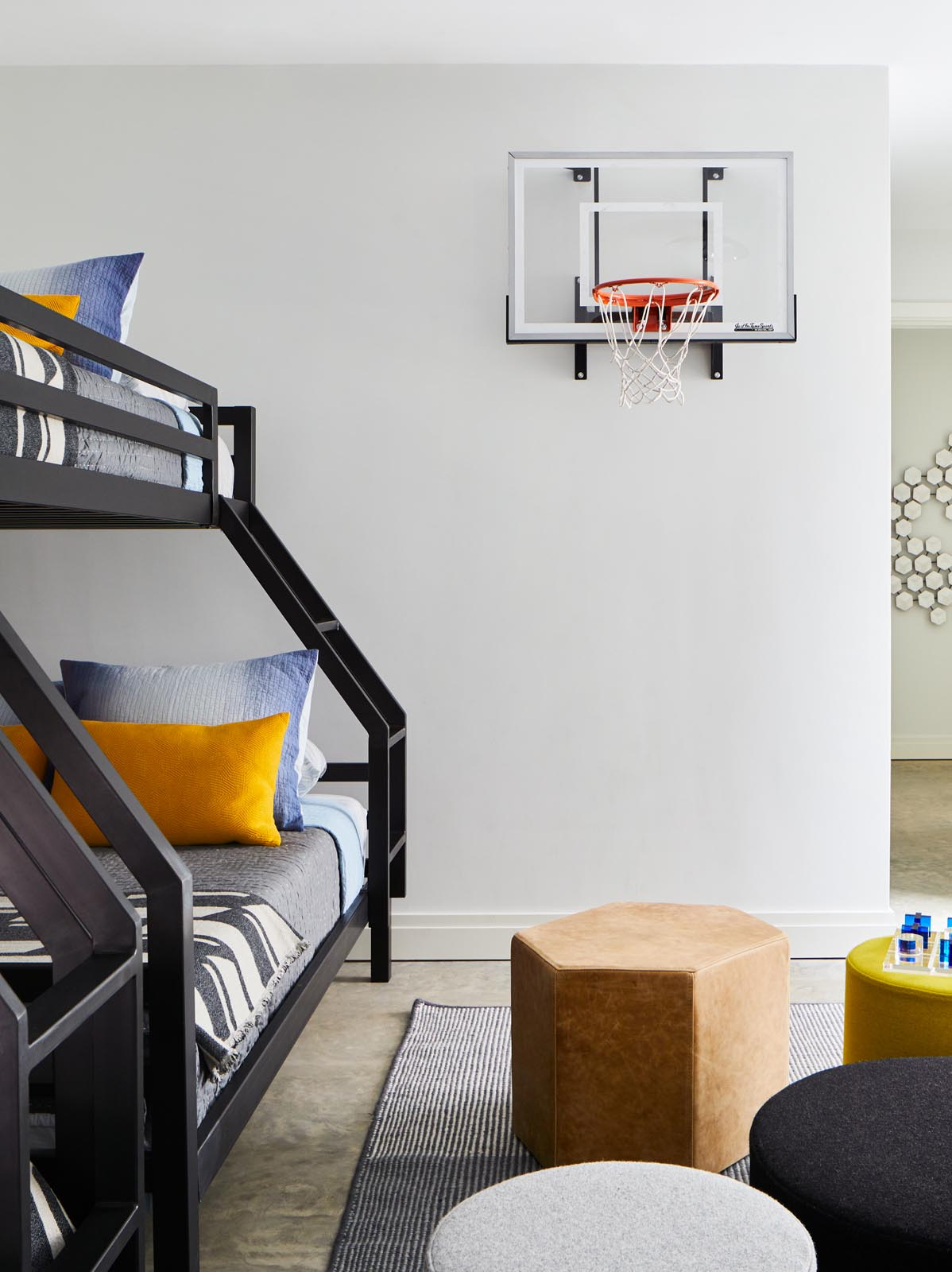 A kids bedroom with bunk beds and a basketball hoop.