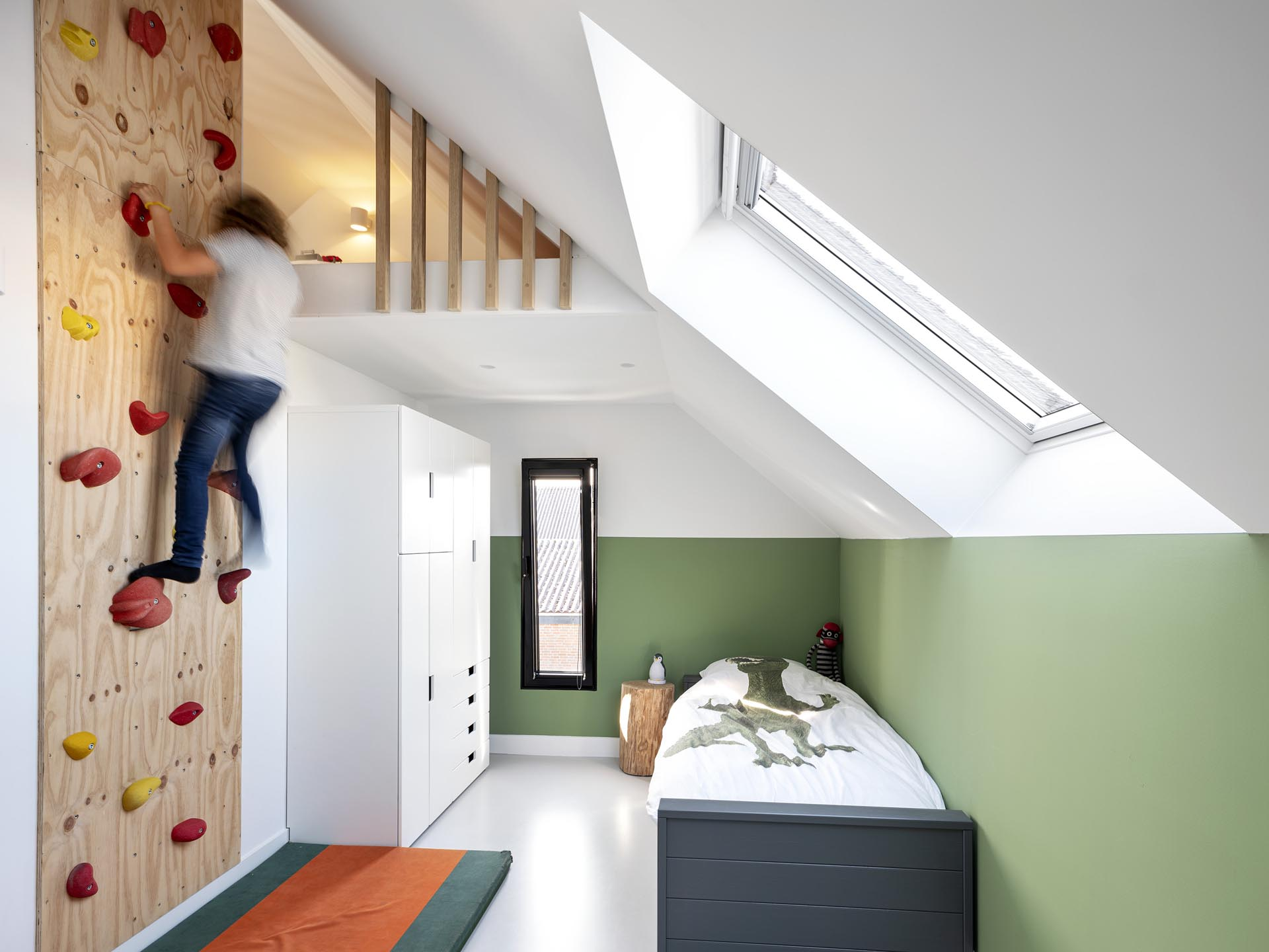 In this modern child's bedroom, there's a rock climbing wall that allows for access to a small lofted area.