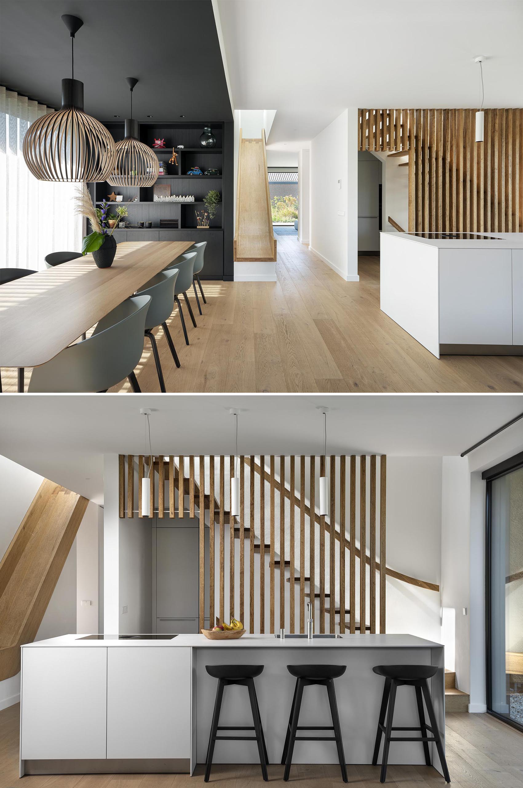 A modern home with an open plan dining room and kitchen. Black has been used on the wall and ceiling to define the dining room, while the kitchen has a wood slat backdrop that acts as a safety barrier for the stairs.