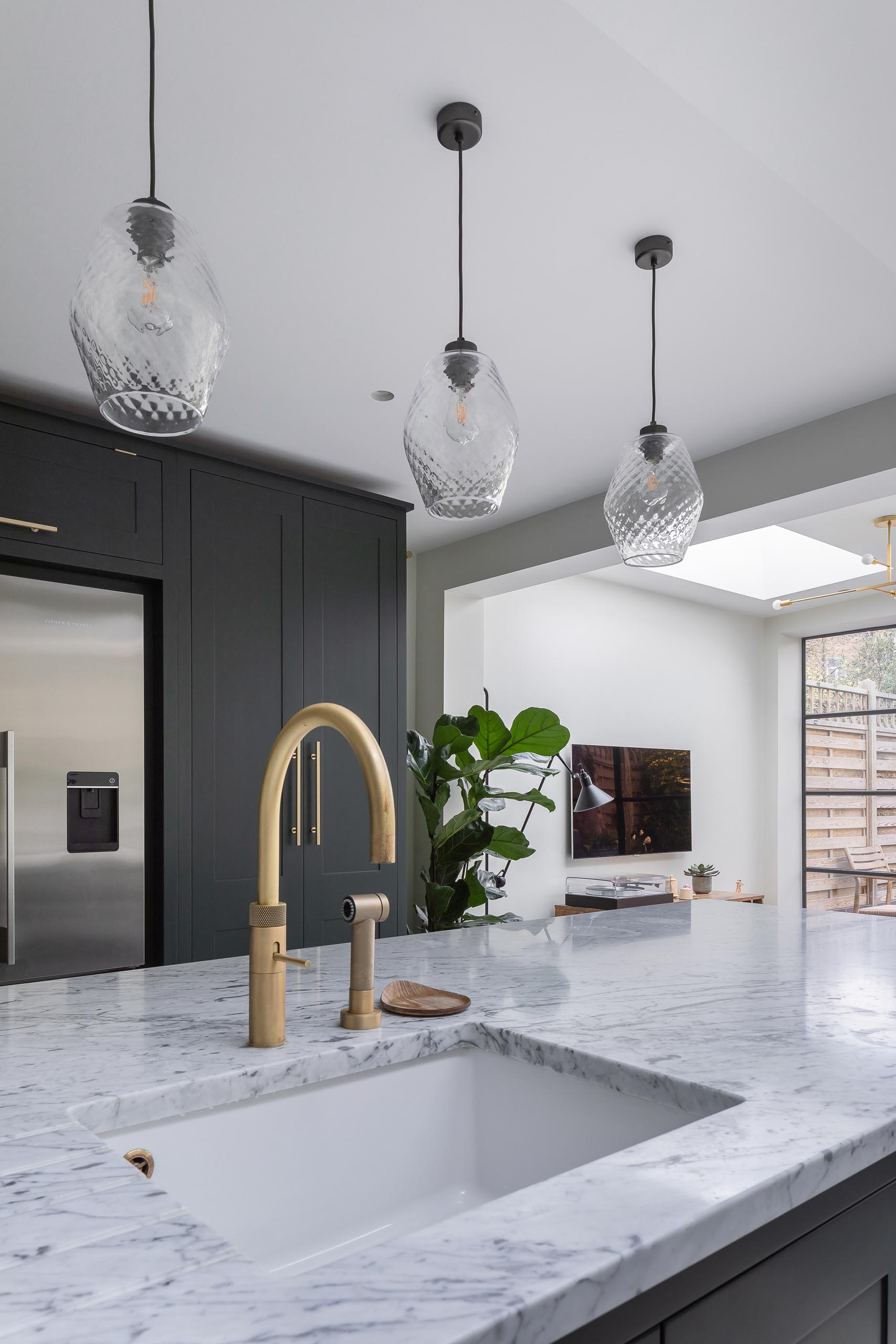 A modern kitchen with dark cabinets that have been paired with gray marble countertops and brass fixtures.