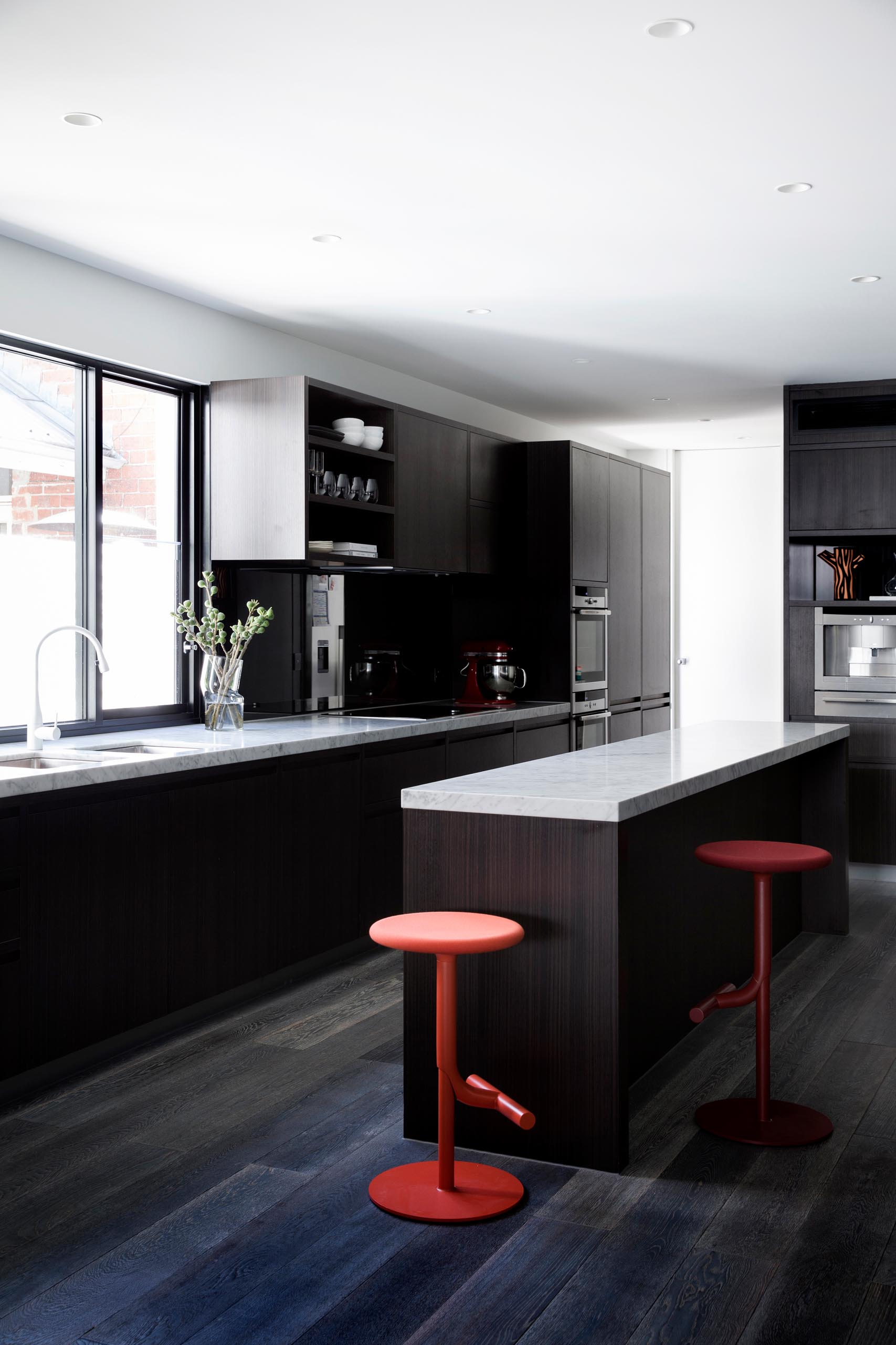 A modern kitchen with dark wood cabinets and light gray marble countertops.