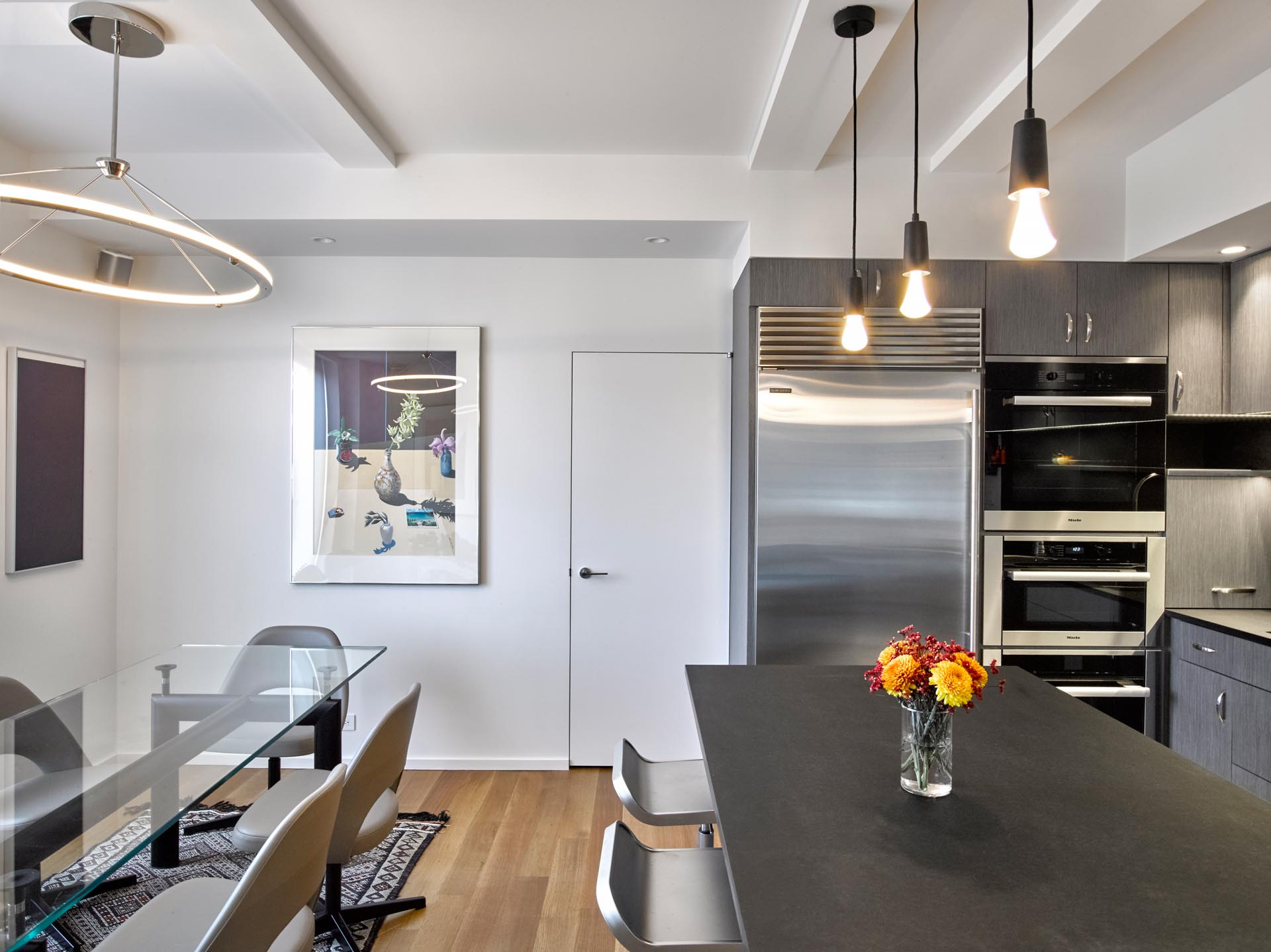 A modern kitchen with gray cabinets, LED undermount lighting, and Paperstone countertops and backsplash.