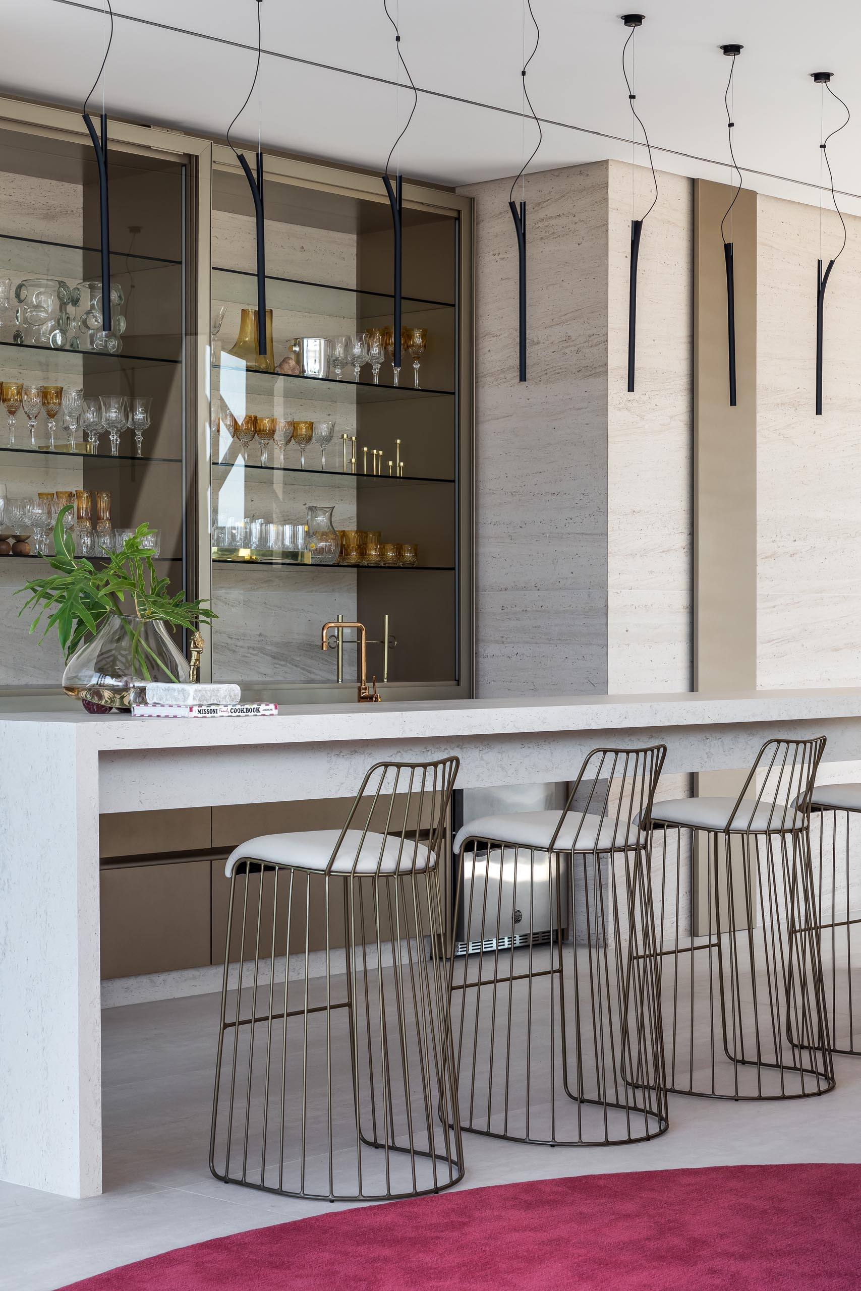 This modern home bar has a long narrow island and glass shelving.
