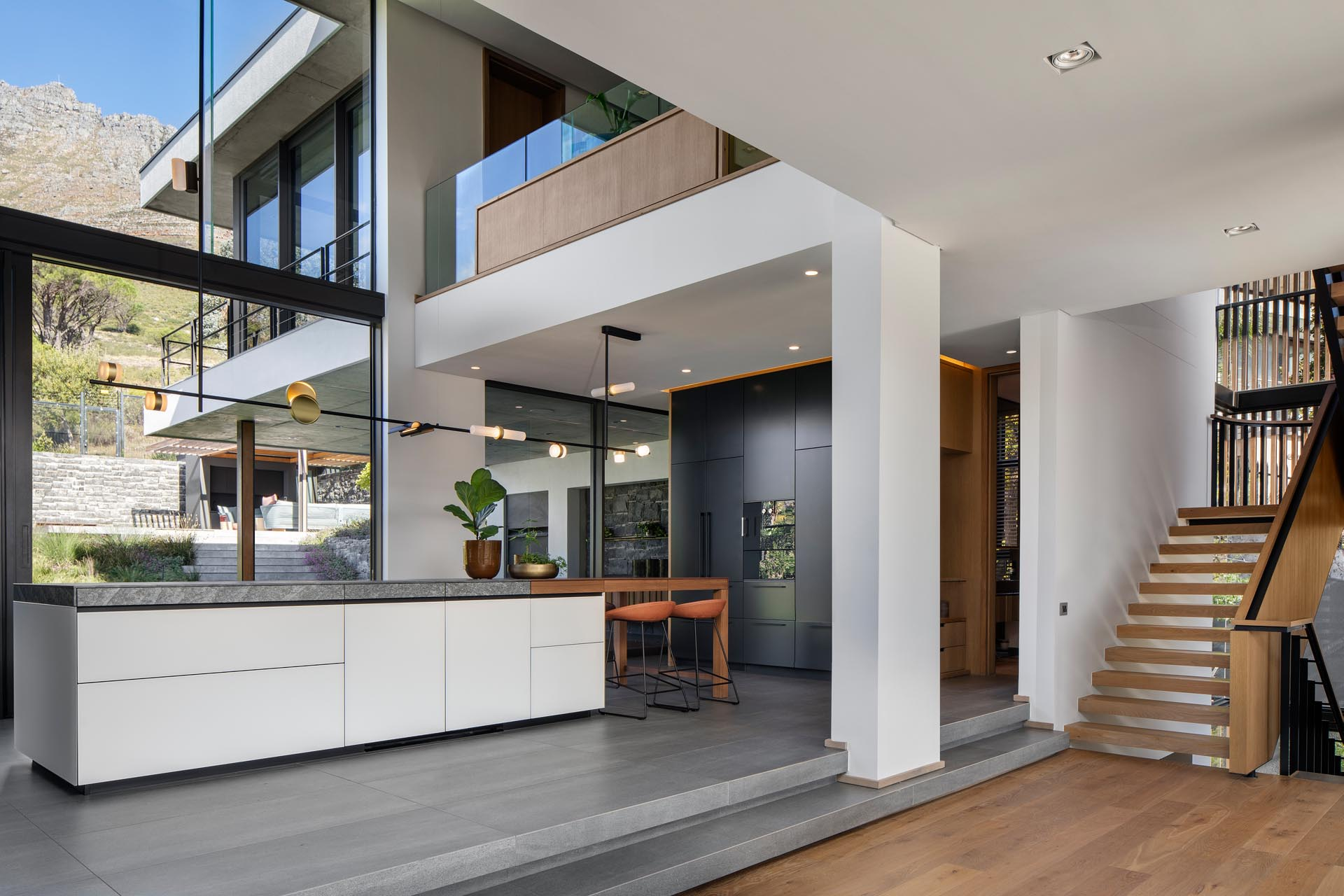 A modern kitchen with minimalist cabinets, a high ceiling, and plenty of windows.