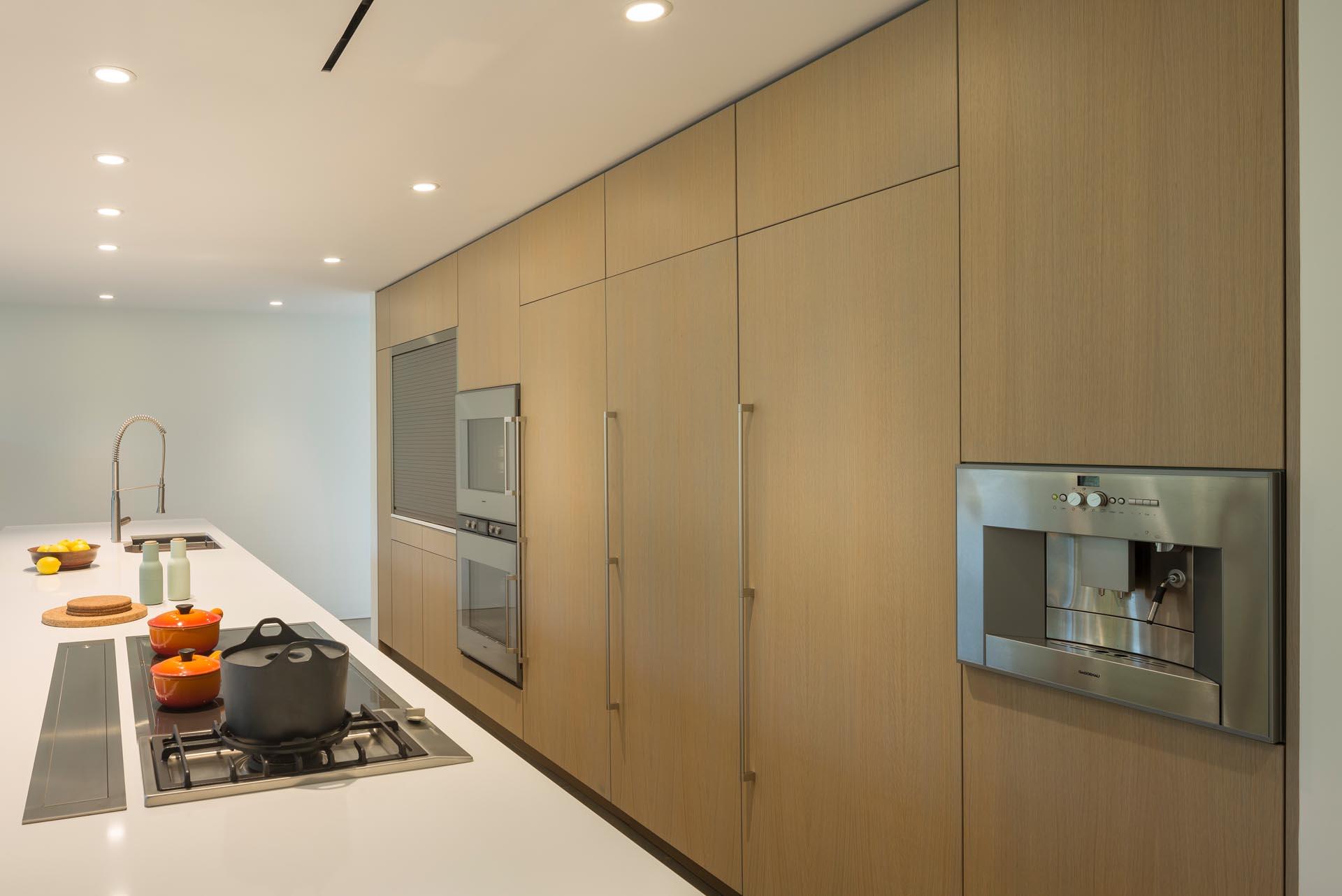 A modern kitchen with minimalist wood cabinets.