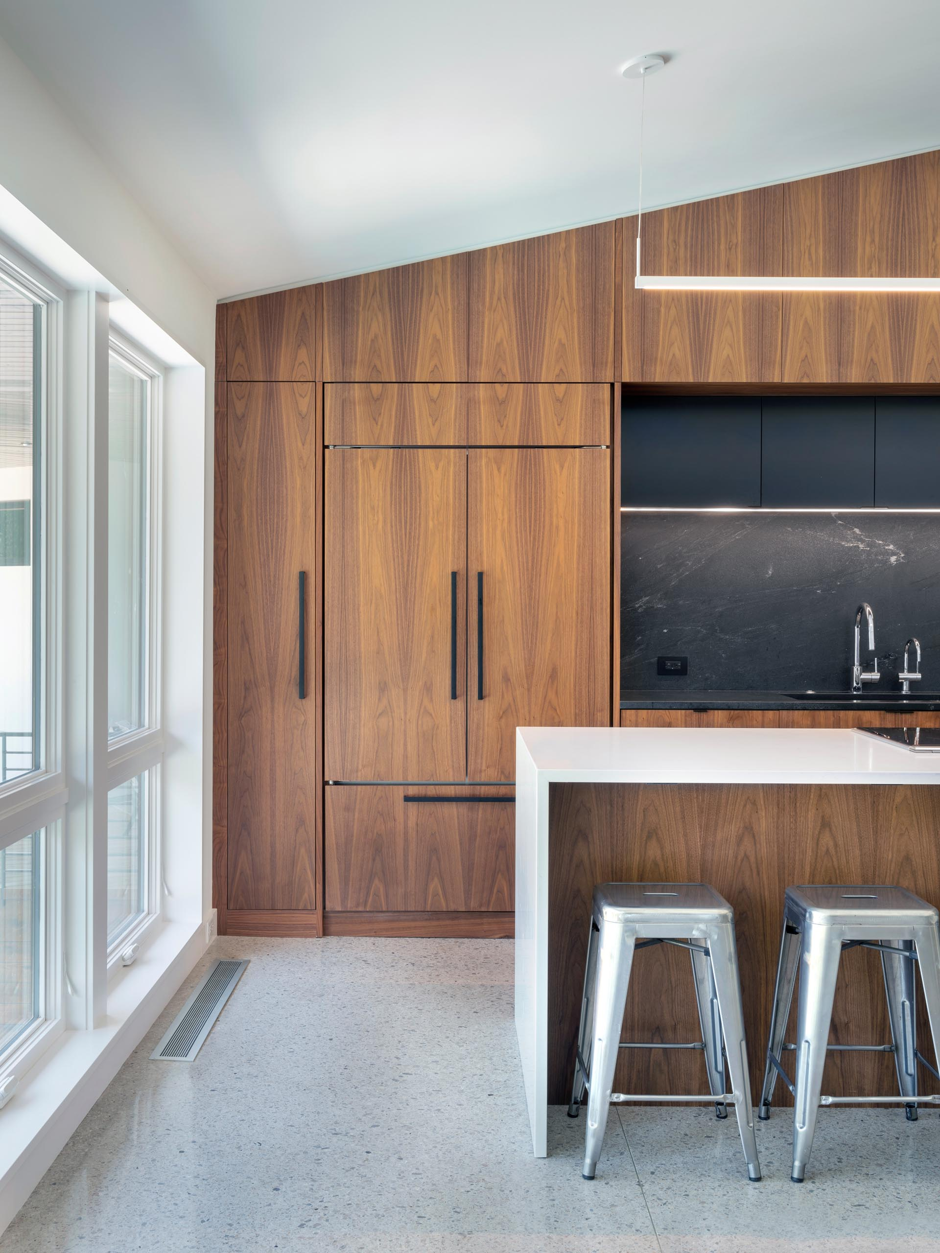 Modern wood kitchen with black backsplash and an island with a white waterfall countertop.