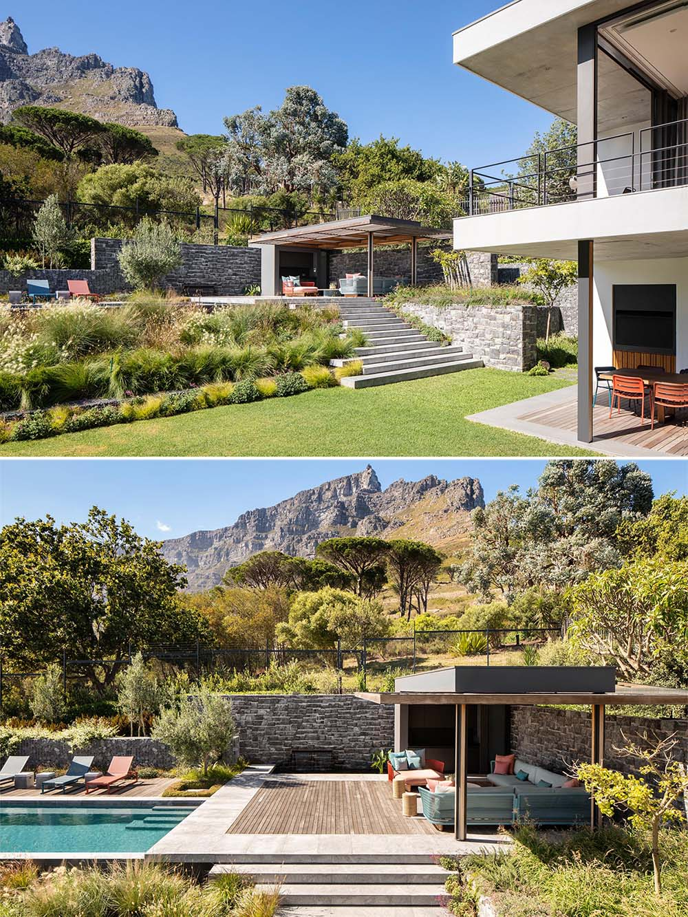 A landscaped yard with an upper level that's dedicated to a swimming pool and pergola.
