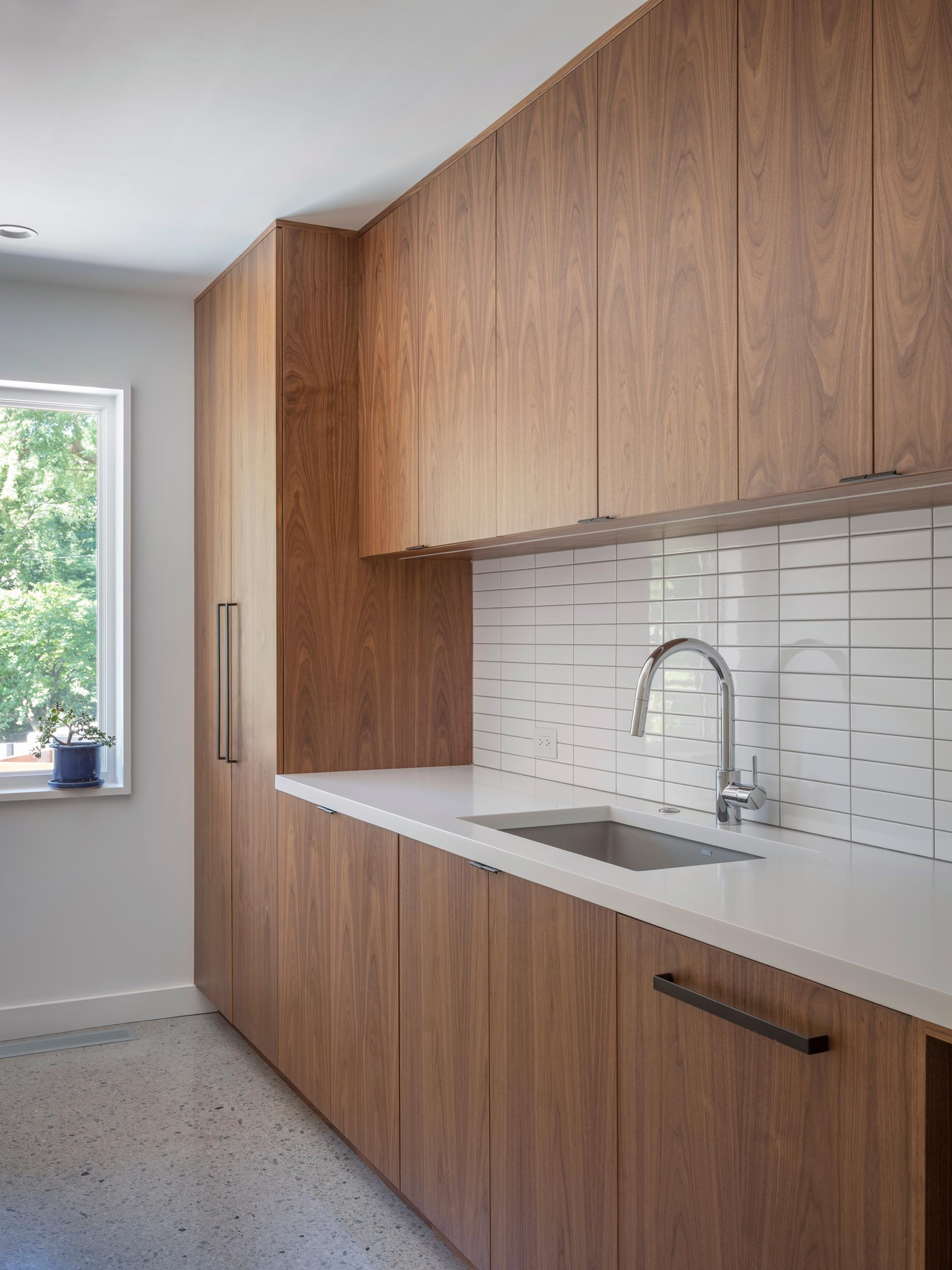 A modern laundry room with wood cabinets, a white countertop, undermount sink, and white subway tiles.