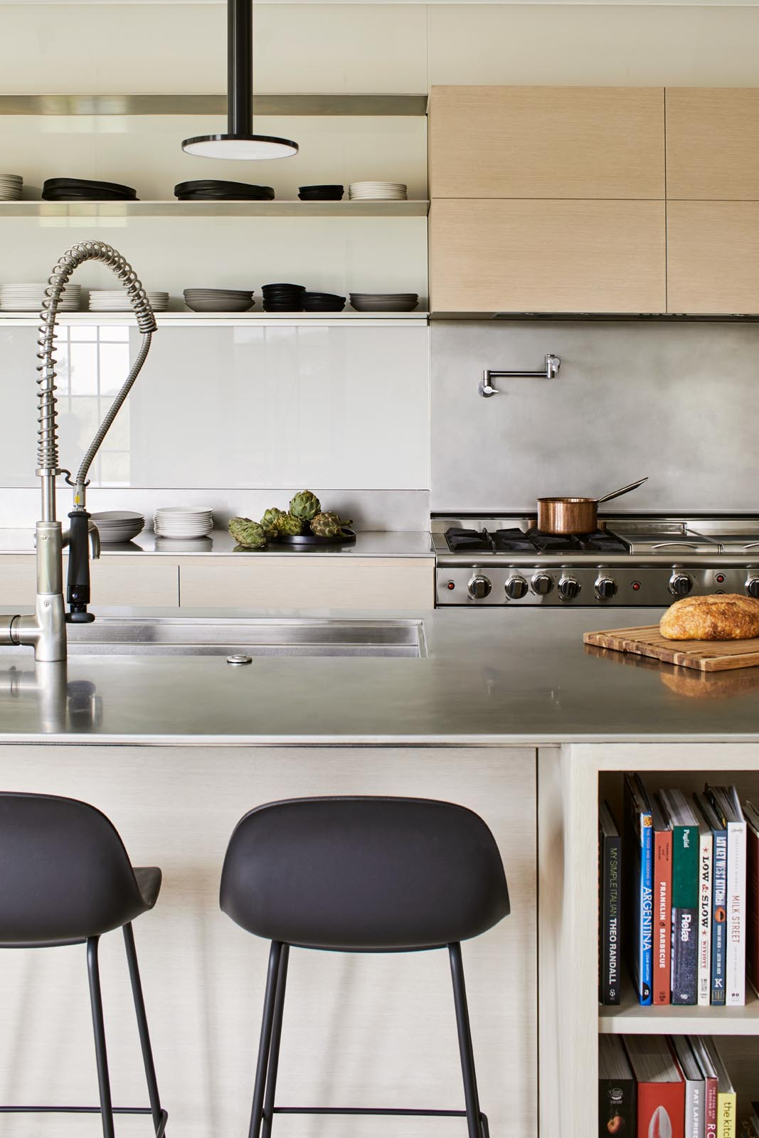 In the kitchen, there's minimalist light wood cabinets and a long island with black pendant lights and room for multiple stools.