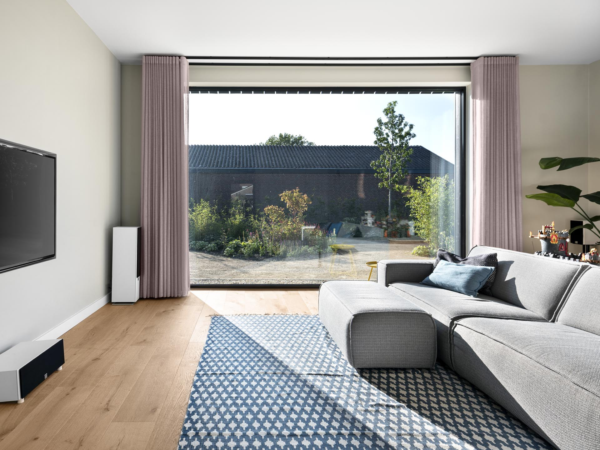 A modern living room with a large window that provides ample natural light and views of the garden.